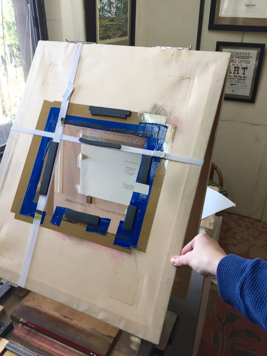 Next, we fold the frisket over the top, so the paper is secure and any non-printing areas protected from ink.