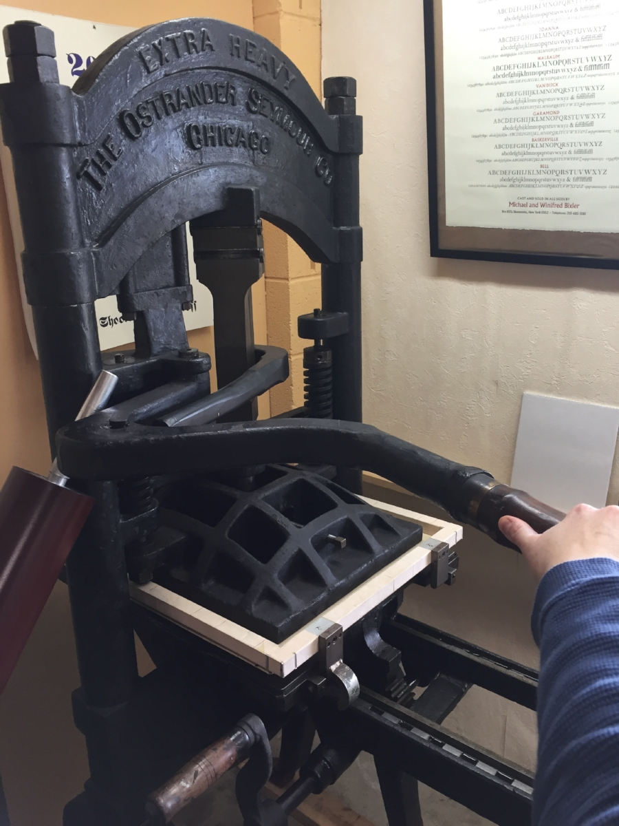 Now we pull the bar ~ this lowers the platen onto the tympan, etc., which presses the paper into the inked type!