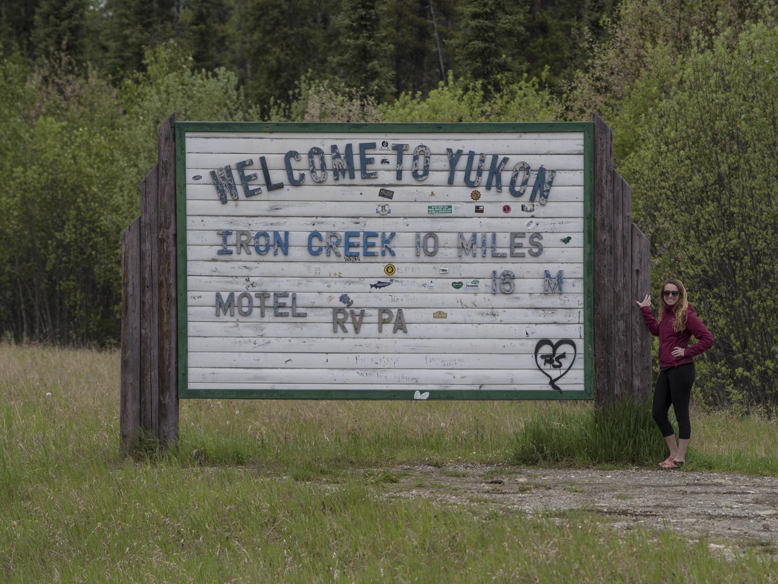 Megan celebrating at the Yukon sign off the Alaskan Highway.