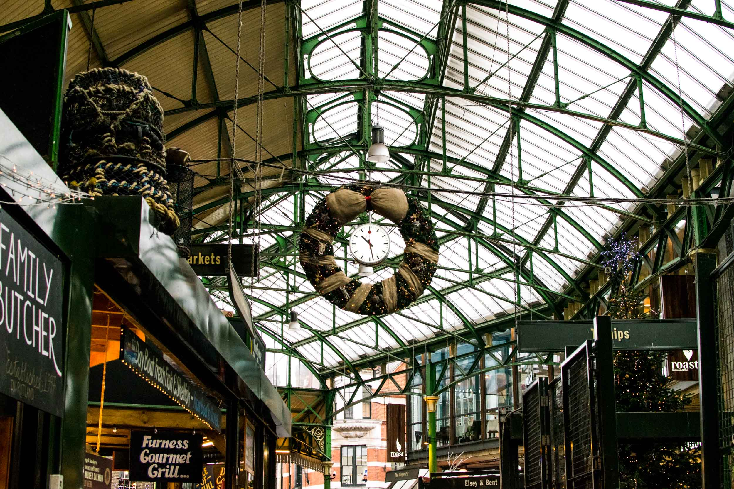 Inside Borough Market, London's oldest market with food stalls, clock and Christmas decorations.
