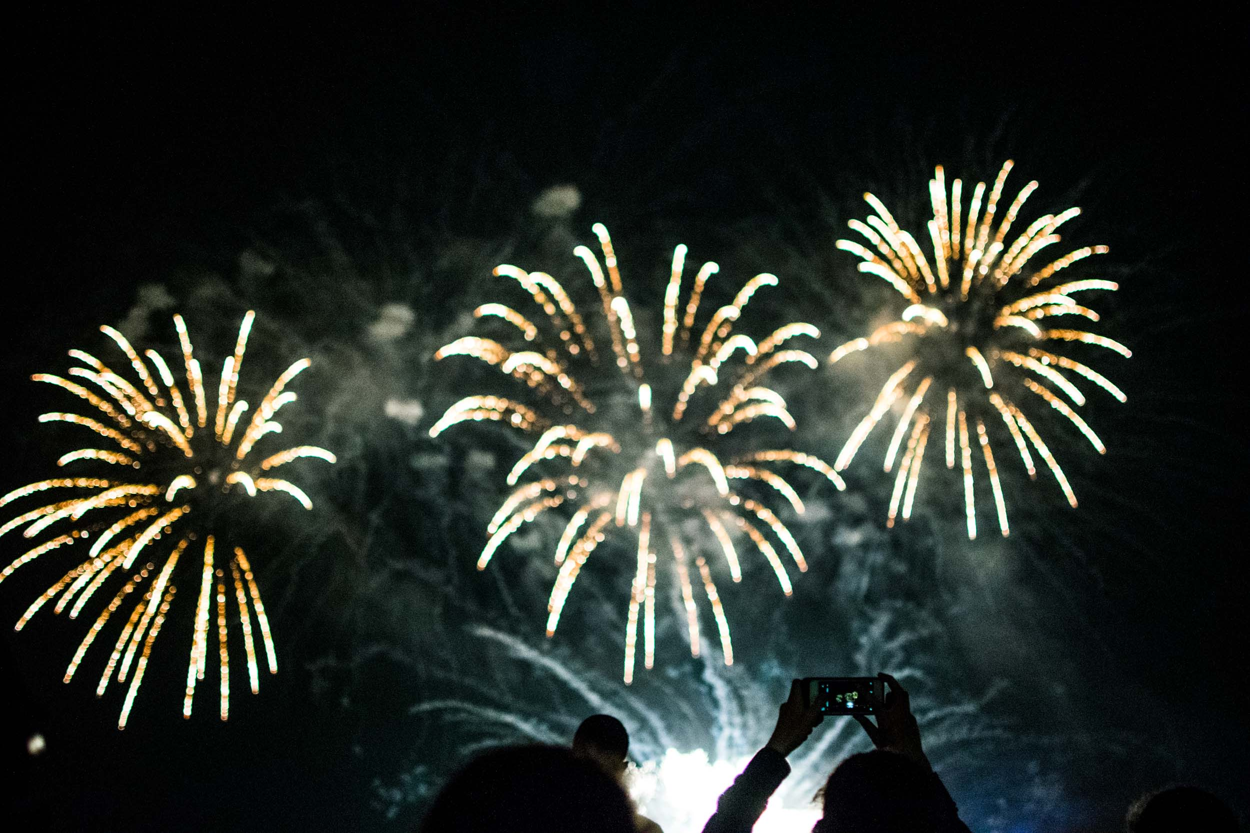 Person capturing the fireworks on their smartphone at the Honda Celebration of Light, English Bay, Vancouver.