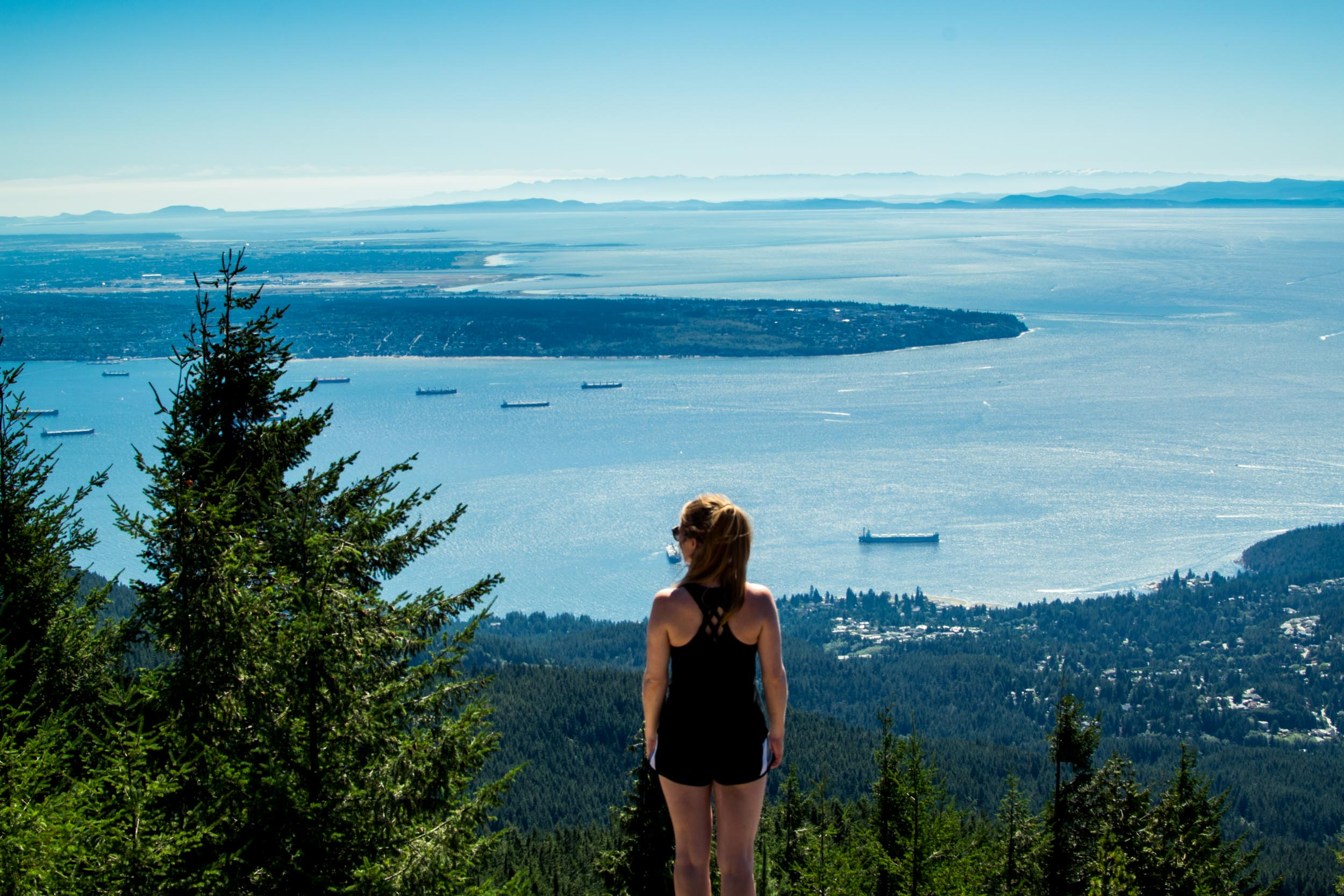 Woman at Eagle Bluffs, a hike on Cypress Mountain, Vancouver with the city and sea below.