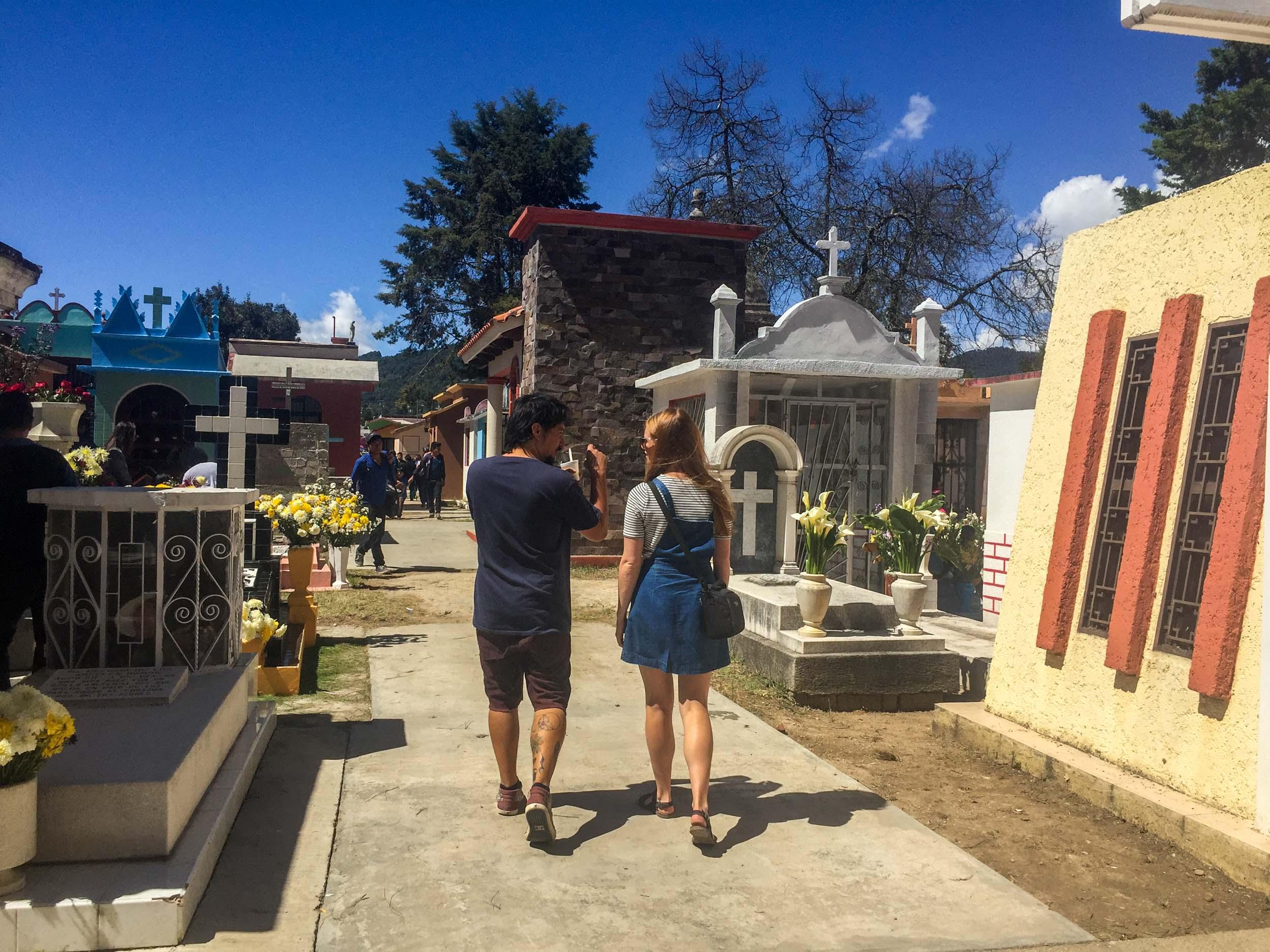 Man and woman walking and talking as they walk through cemetery in San Cristobal de las Casas, Mexico.