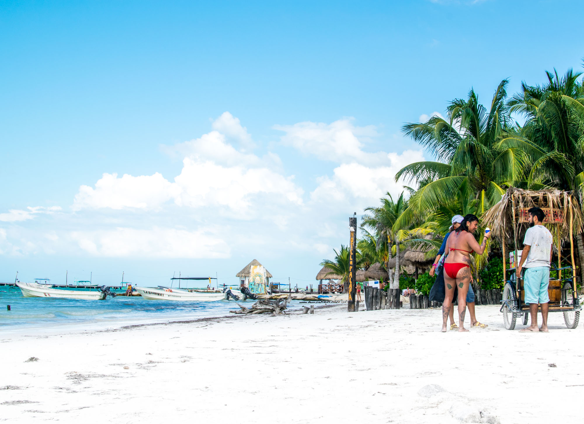 Couple buying shaved coconut from a cart on the beach in Isla Holbox,Mexico.