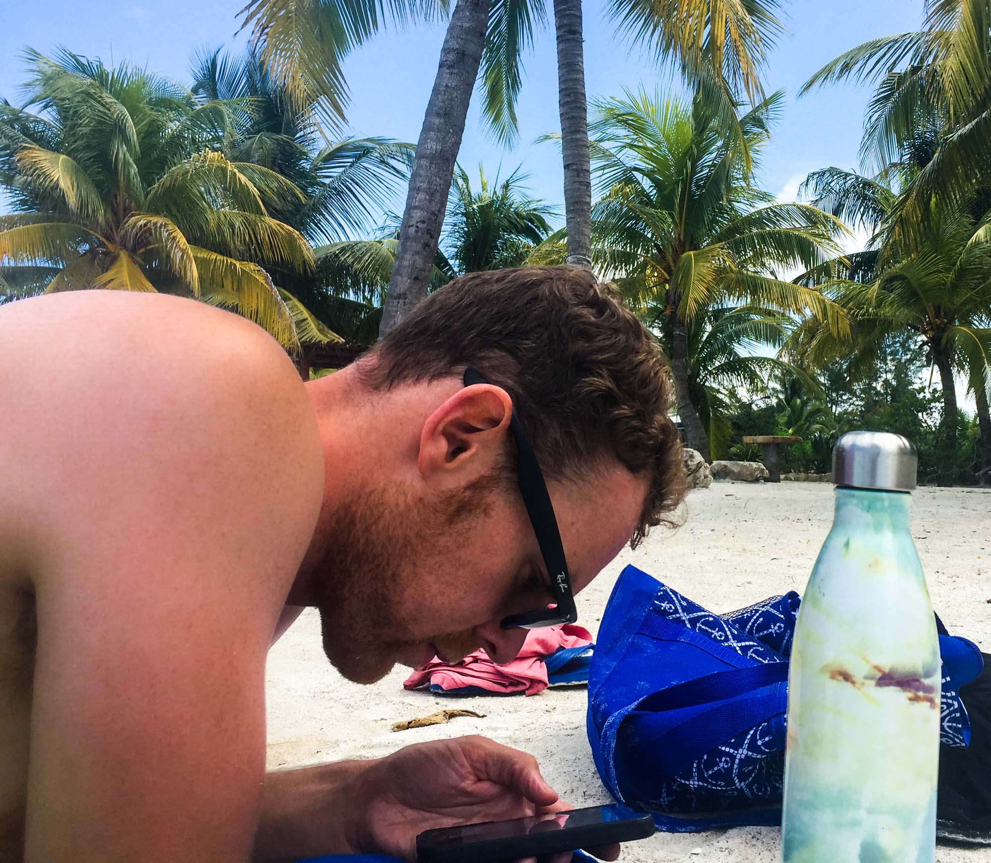 Man looking at iPhone to book flights on beach in Mexico.