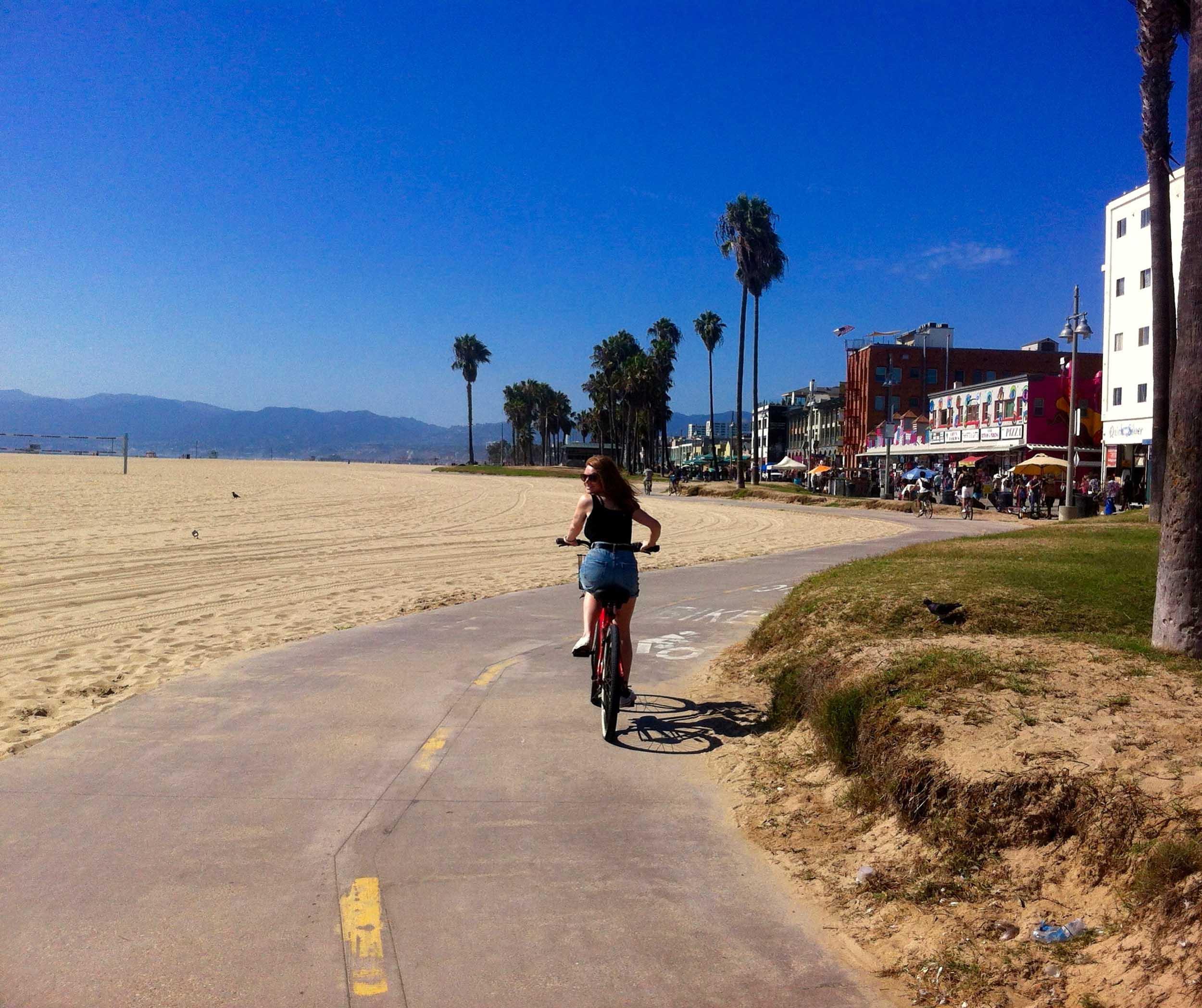 Woman cycling the bike path alongside the beach in Santa Monica, California, USA.