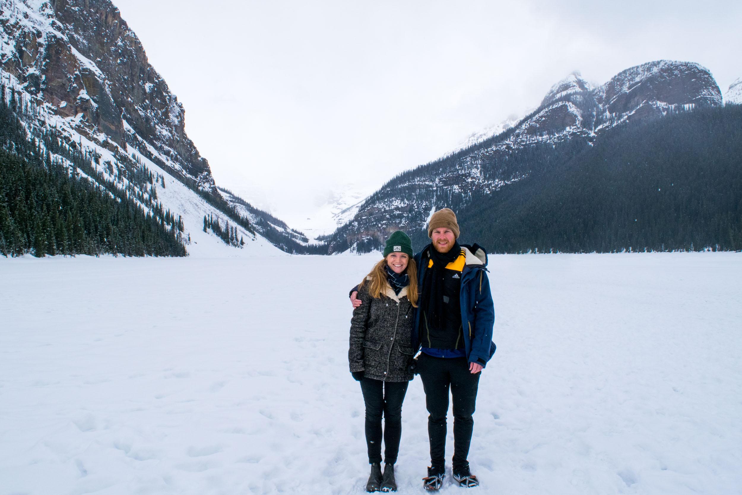 Couple stood on a frozen Lake Louise, near Banff, Alberta, Canada.