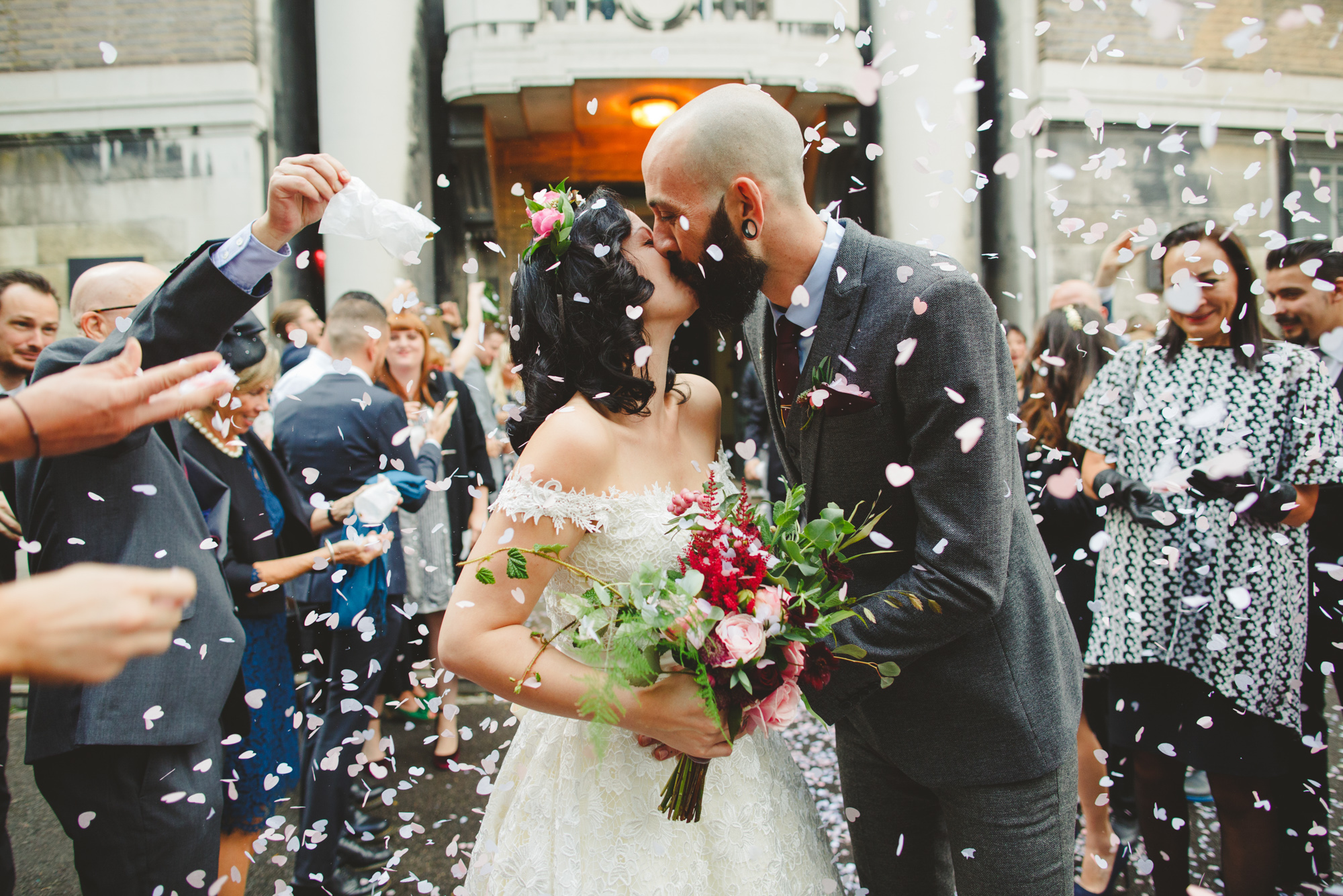 Wedding photograph of Bride in vintage dress and alternative groom  at Town Hall london wedding covered in confetti by Camera Hannah.