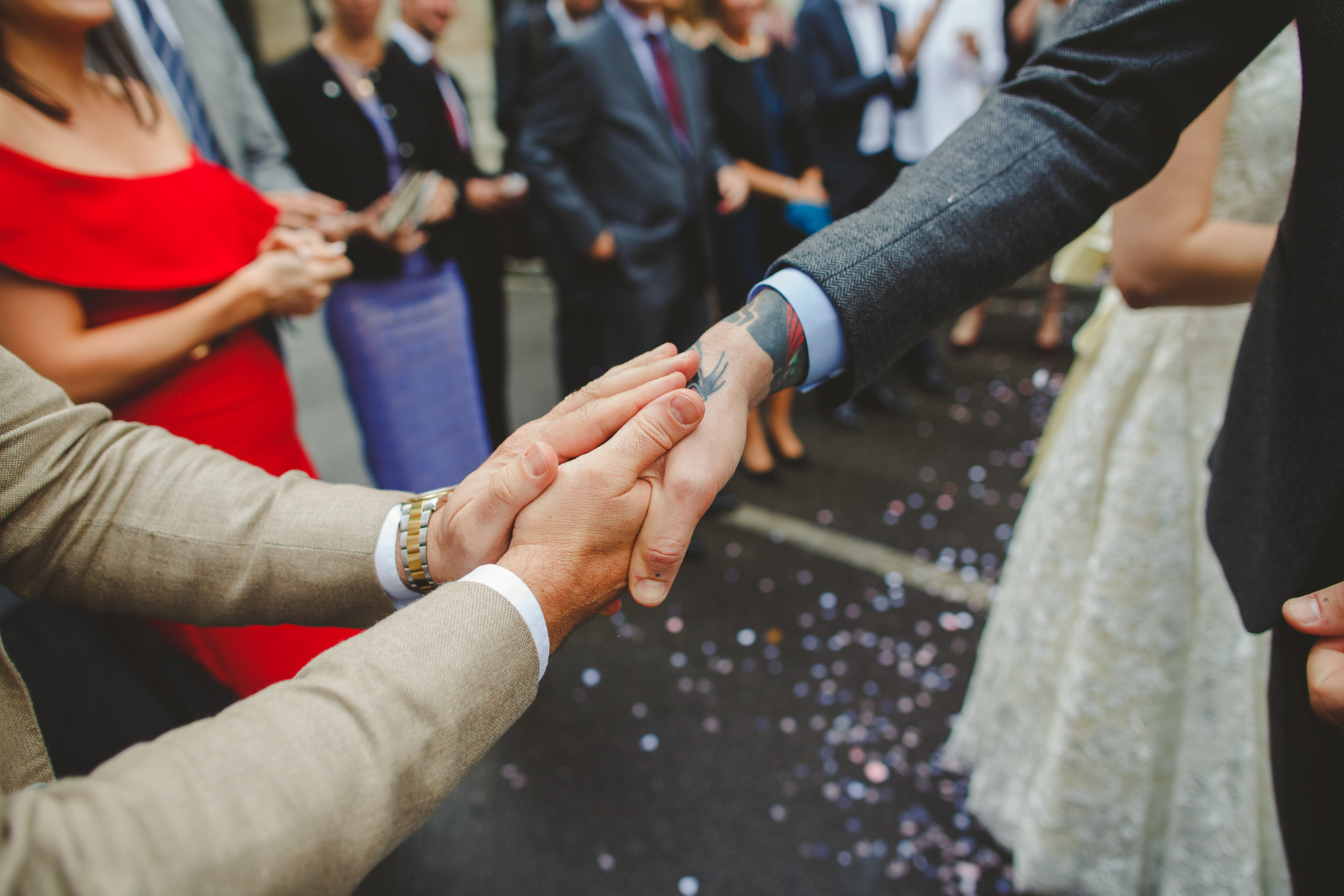 reportage wedding photo, groom shaking hands at London wedding