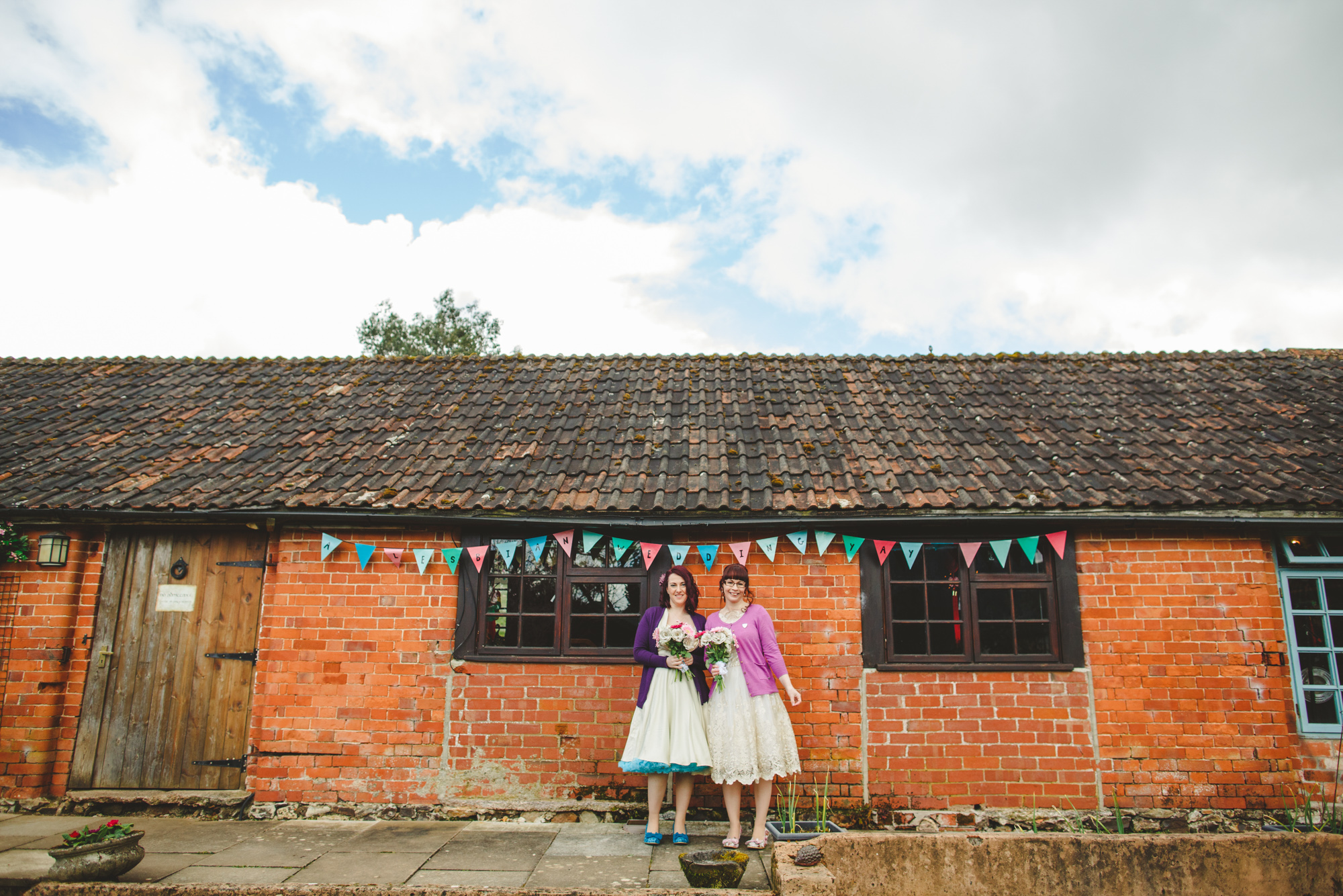 same sex wedding couple in fifties style dresses with petticoats by pretty barn venue