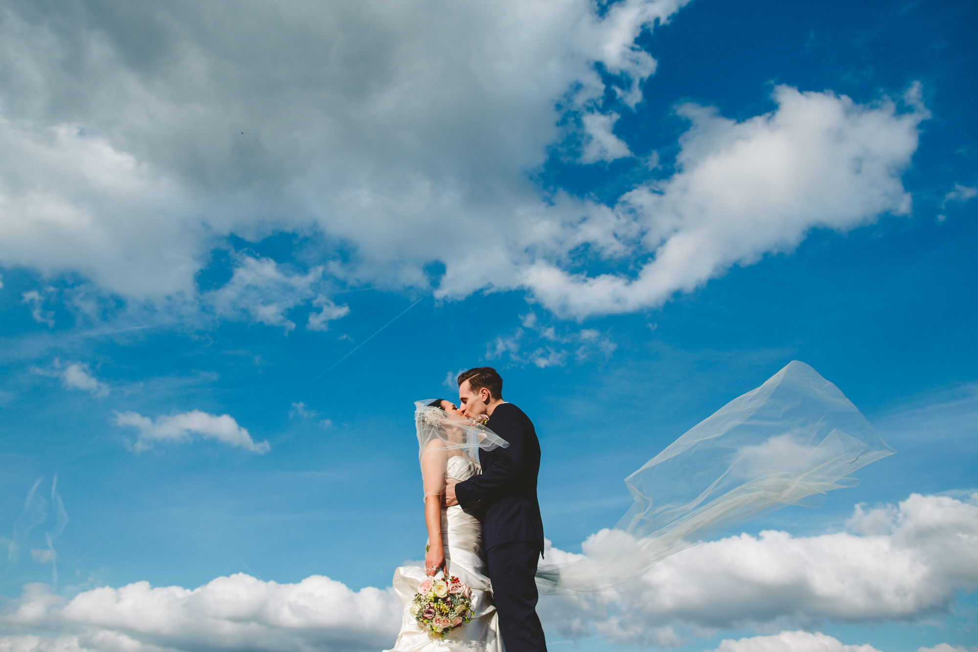 kissing couple against blue sky wedding photo