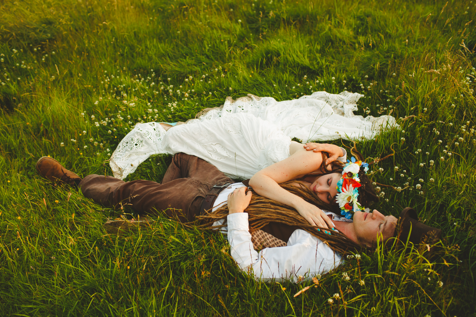 hippy wedding couple lying in grass photo