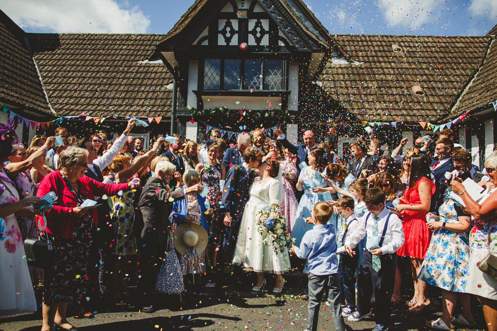 cute vintage village hall wedding, guests throwing rainbow confetti on bride and groom