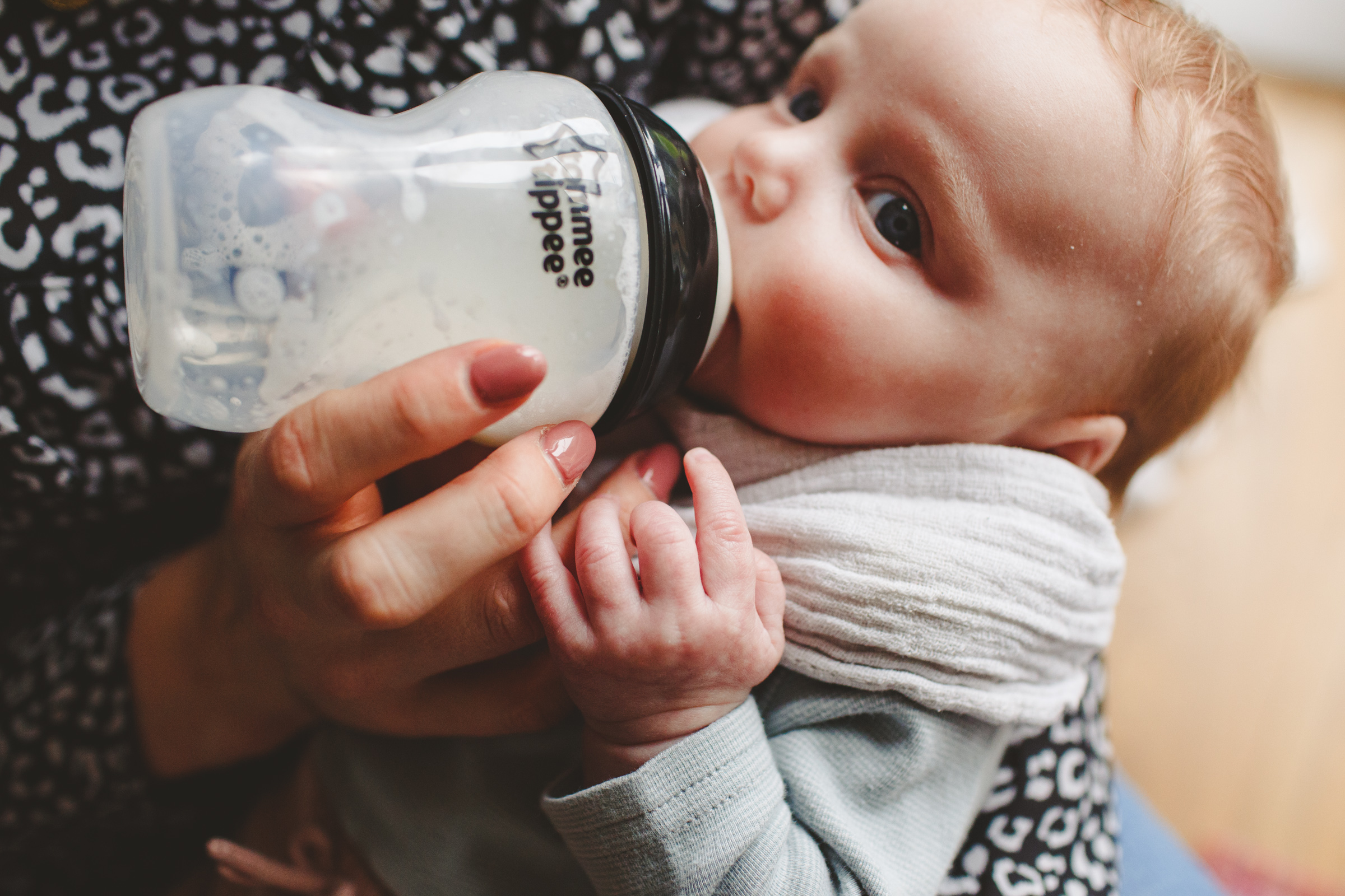 Baby drinking from bottle during family photoshoot