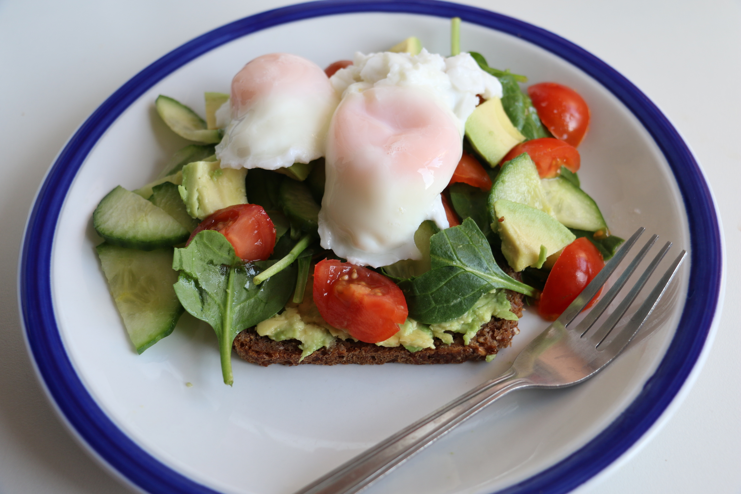 Two poached eggs, one slice of rye bread with half an avocado crushed onto it. Cherry tomato, cucumber and spinach too.