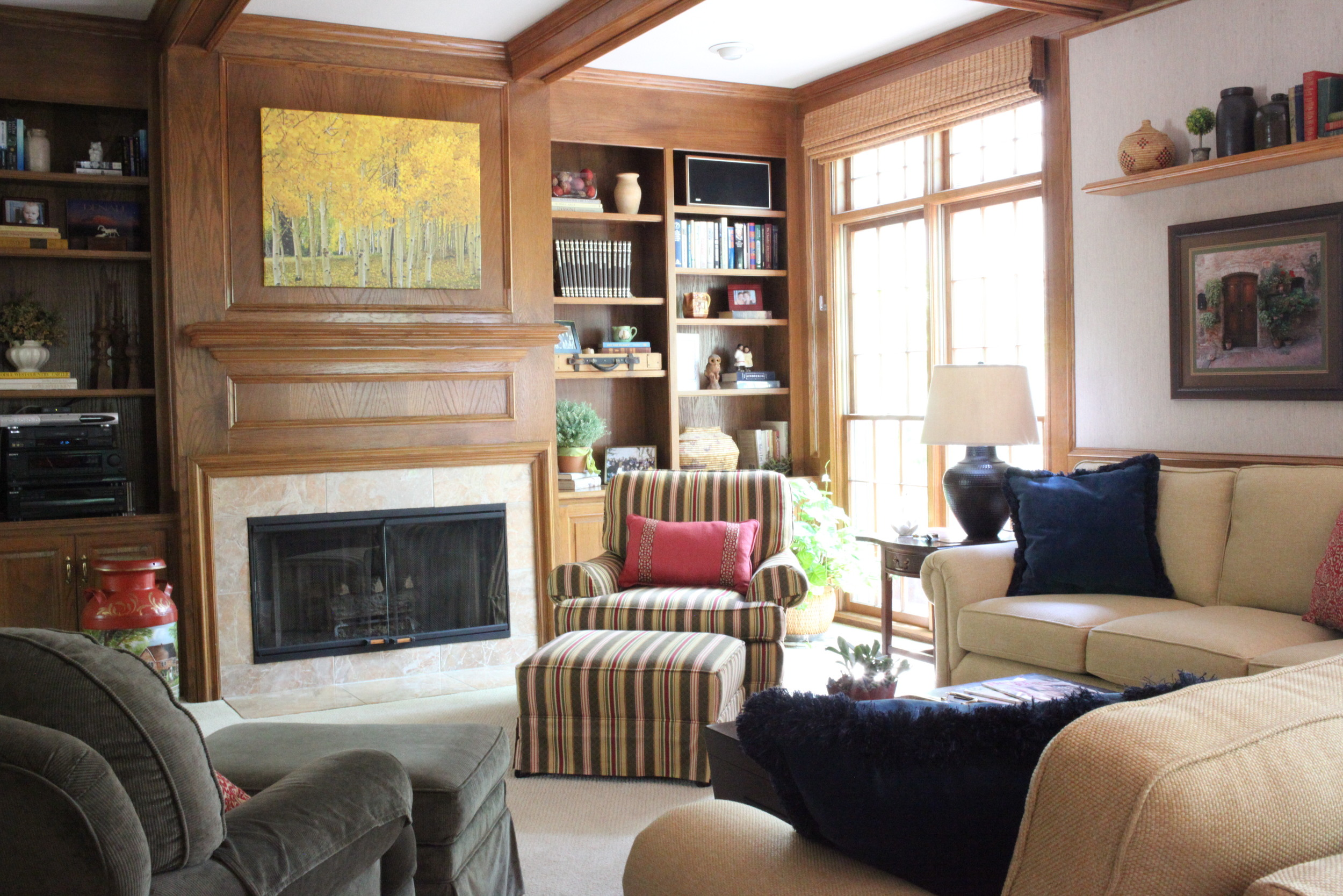 Coffered ceiling cozy living room with fireplace, striped chair, blue pillows, and wood paneling