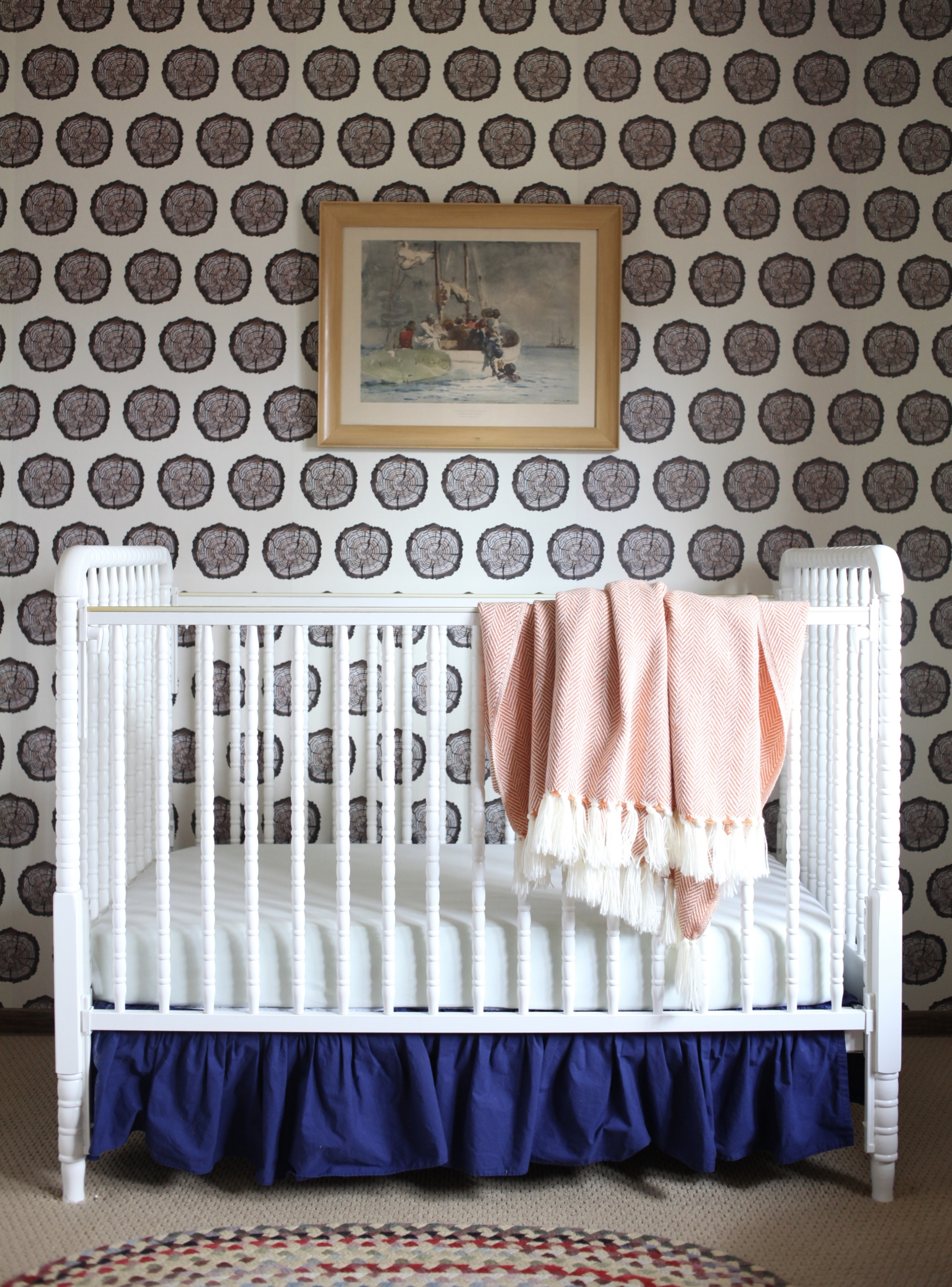 Modern nursery with white Lind crib and modern wood wallpaper