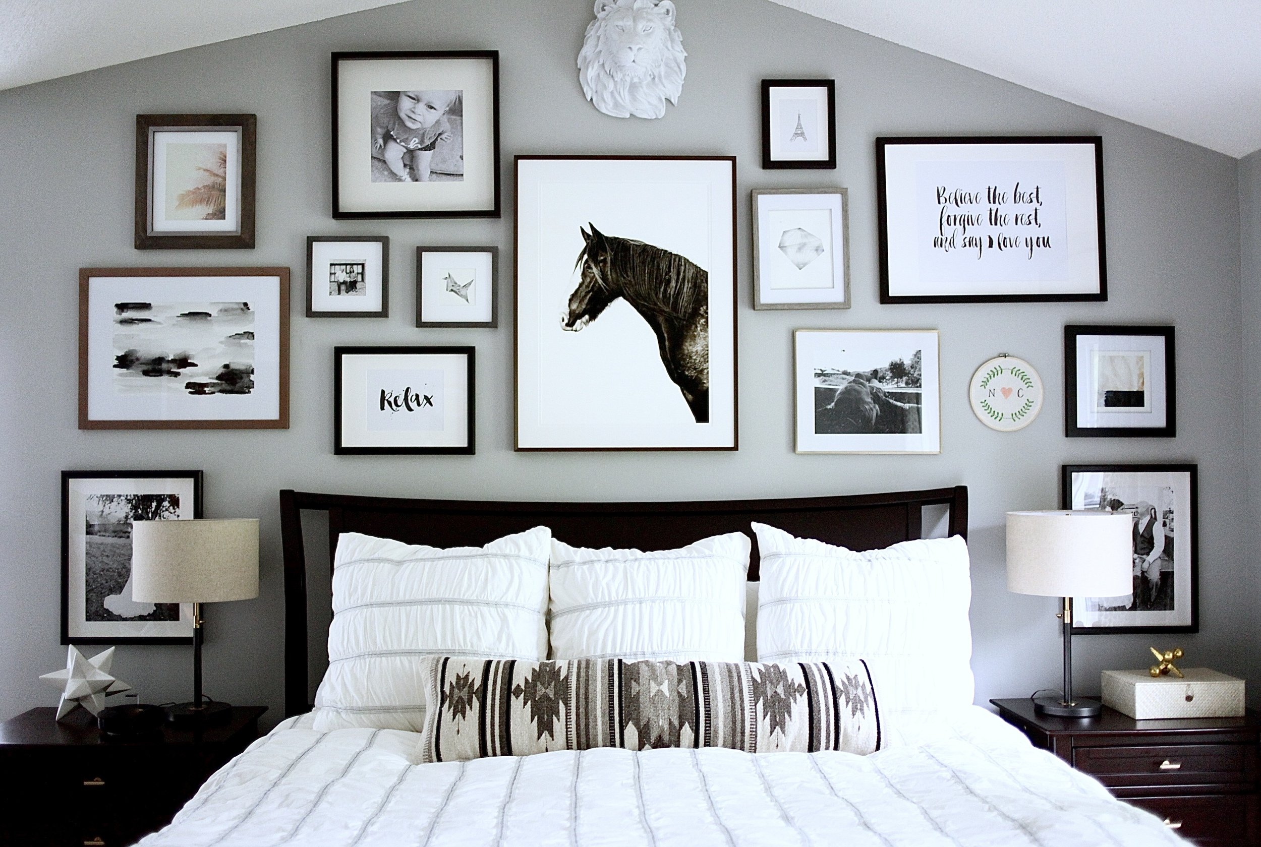 Black and white bedroom with gallery wall above bed, Citizenry Home Goods lumbar pillow, horse photograph and matching lamps