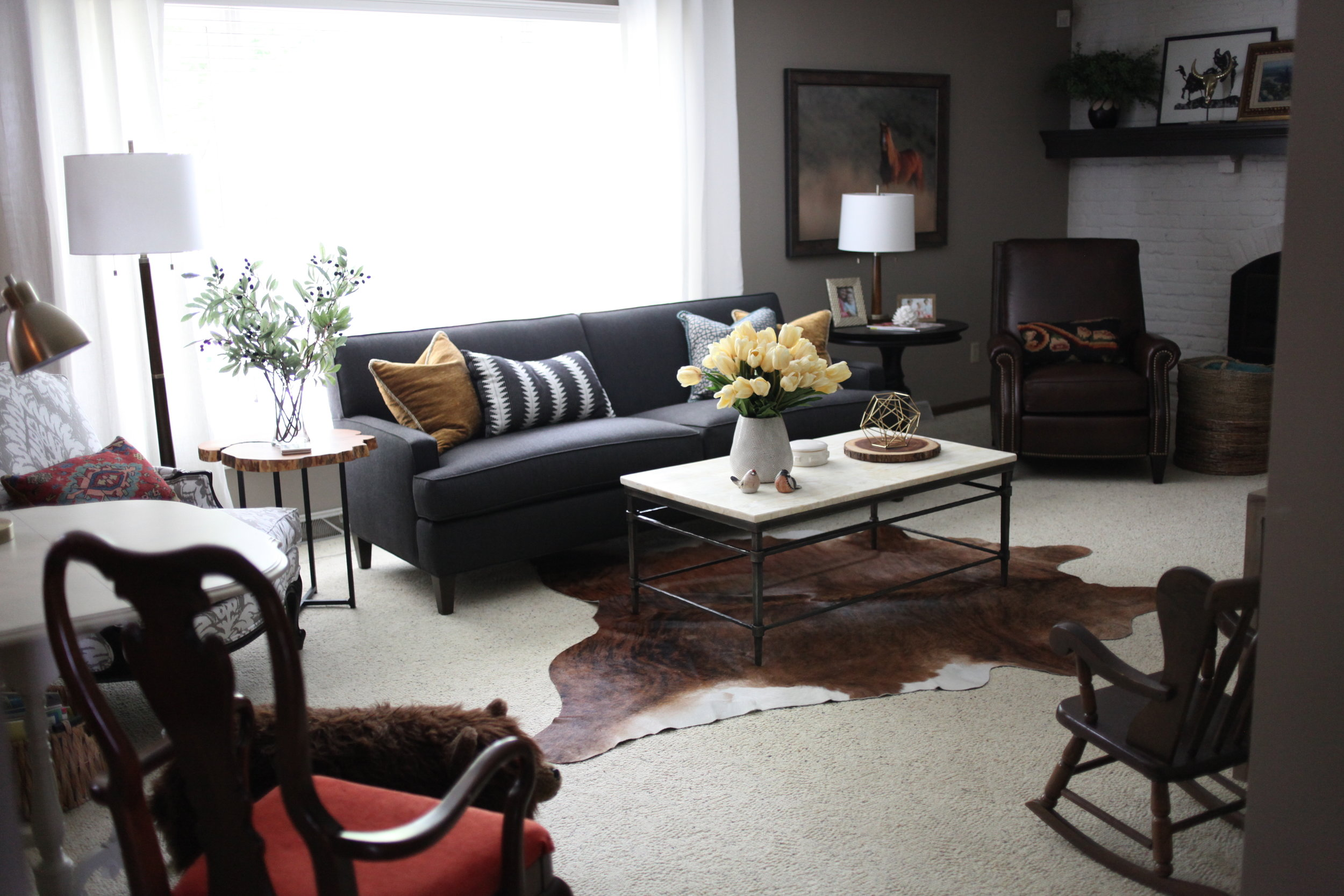 Modern Southwestern living room with grey couch, white painted fireplace, cow hide rug and black and white pillow
