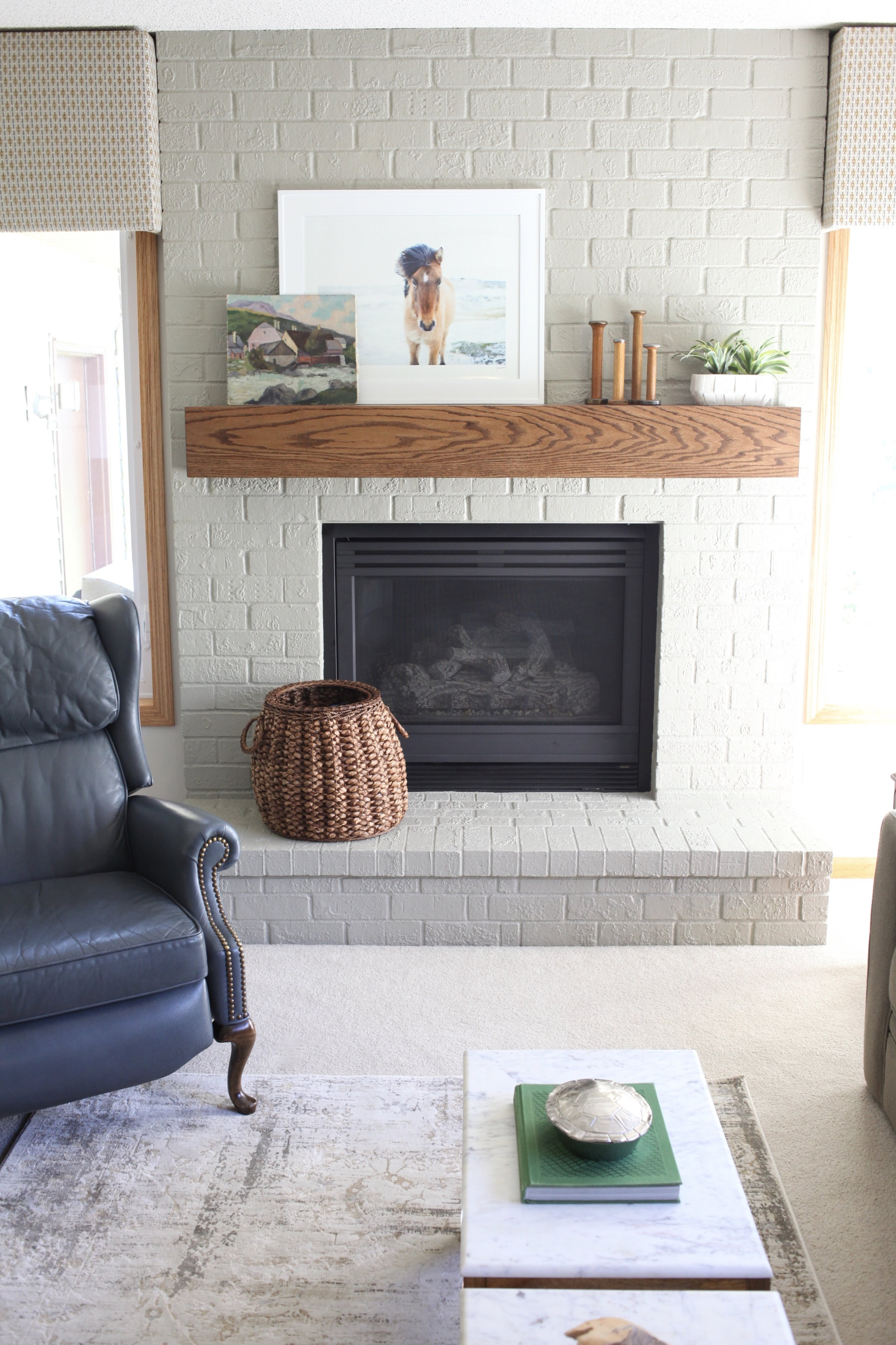 Modern fireplace with wood mantel, horse art, box valences, basket, blue leather chair, silver turtle box