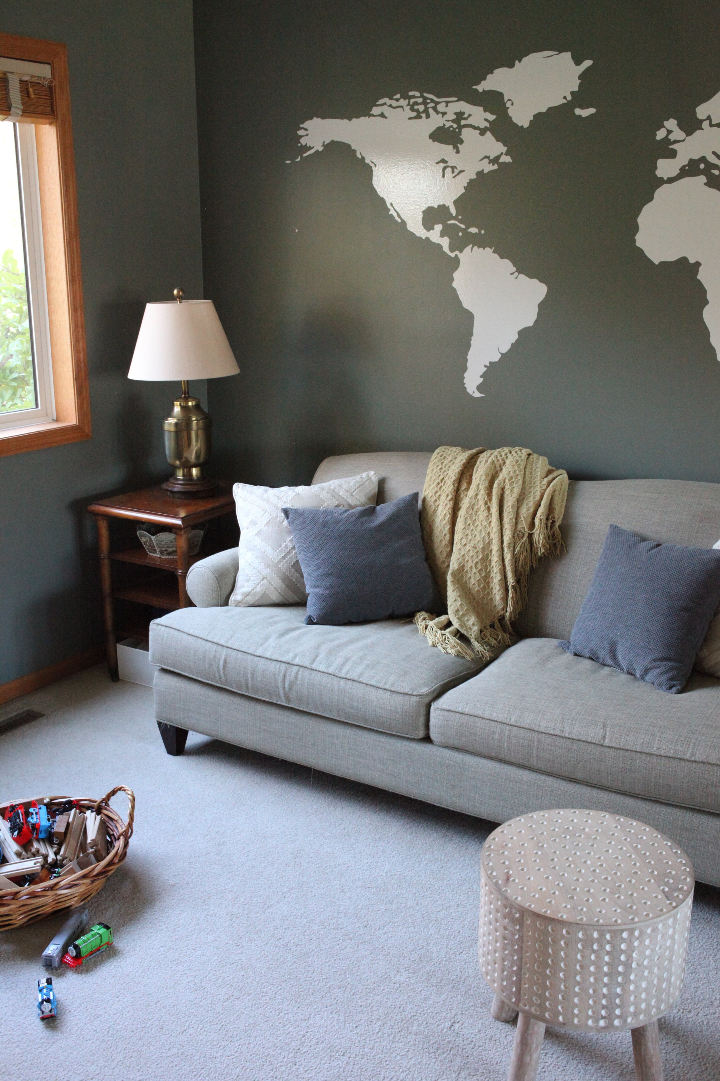 Living room with world decal and cozy sofa.