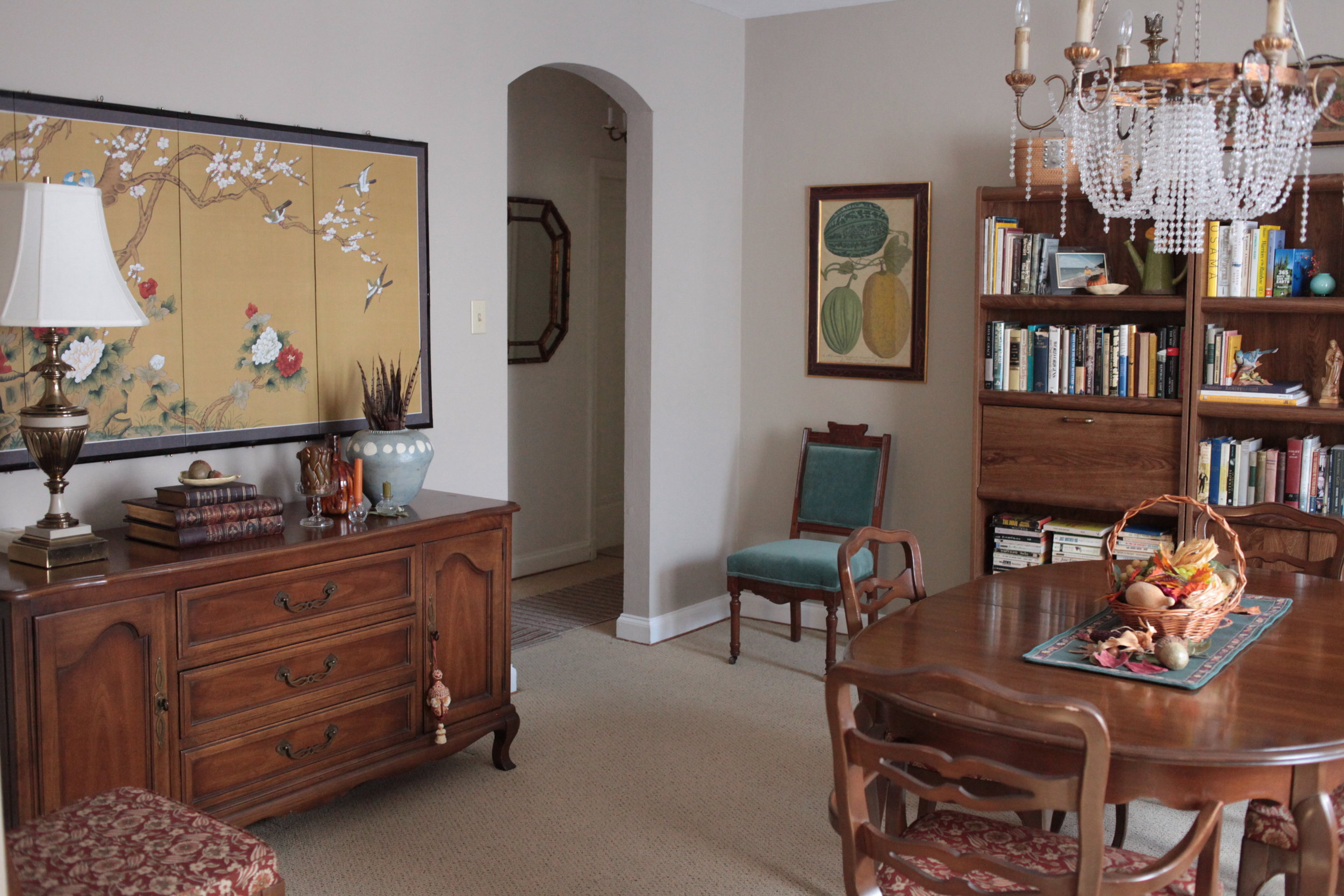 Traditional dining room with silk screen bird art, blue velvet chair, crystal chandelier, and styled bookshelves