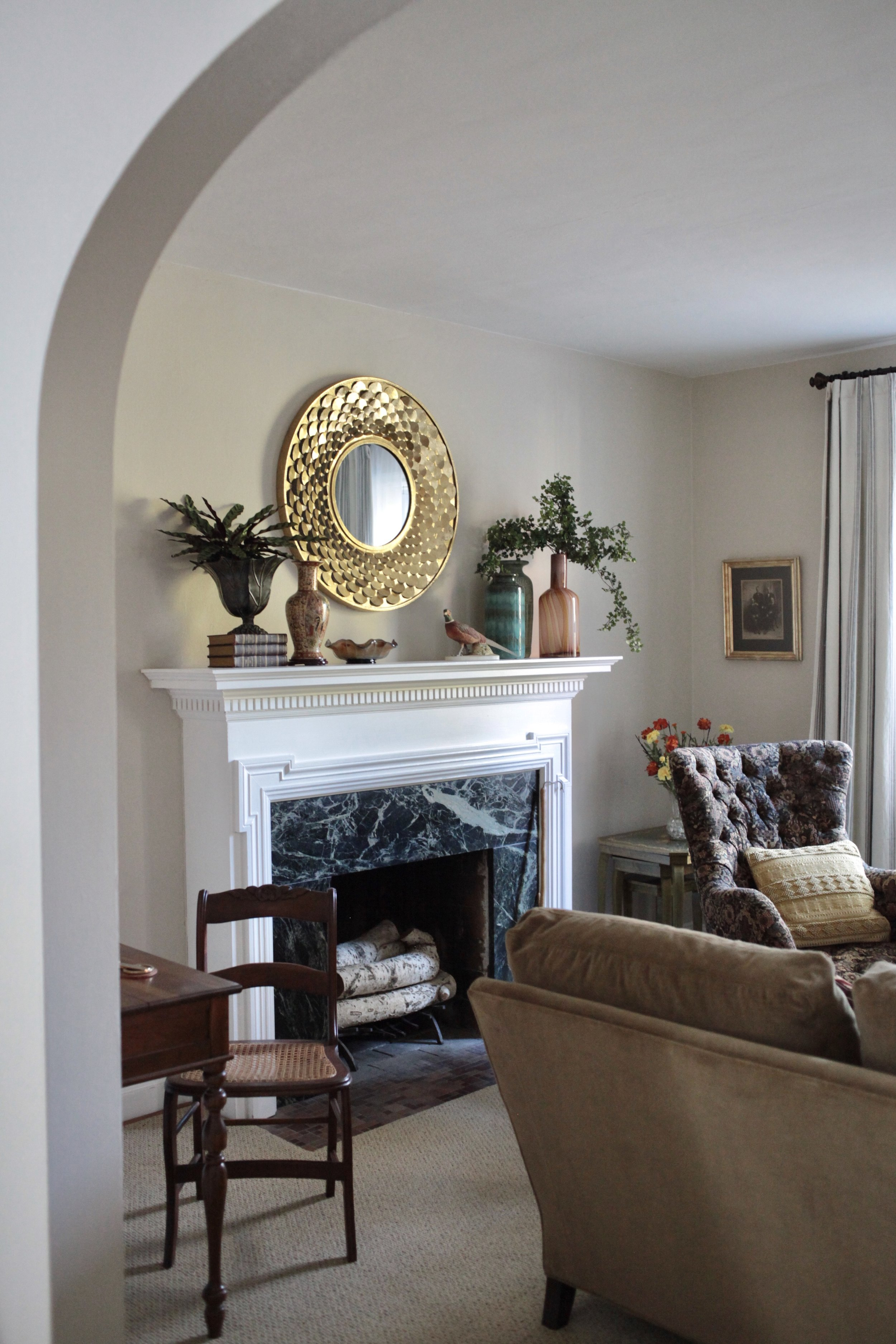Gold round mirror above fireplace