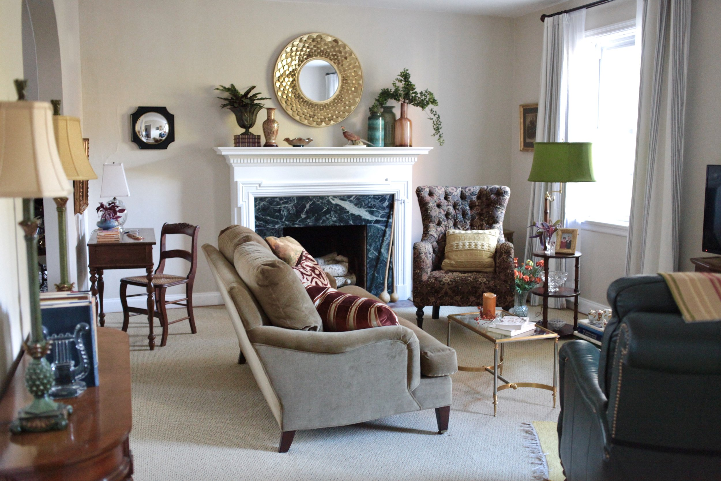 Traditional Living room with floating velvet sofa, white fireplace, green lamp shade, circle mirror, concave mirror, and tufted chair
