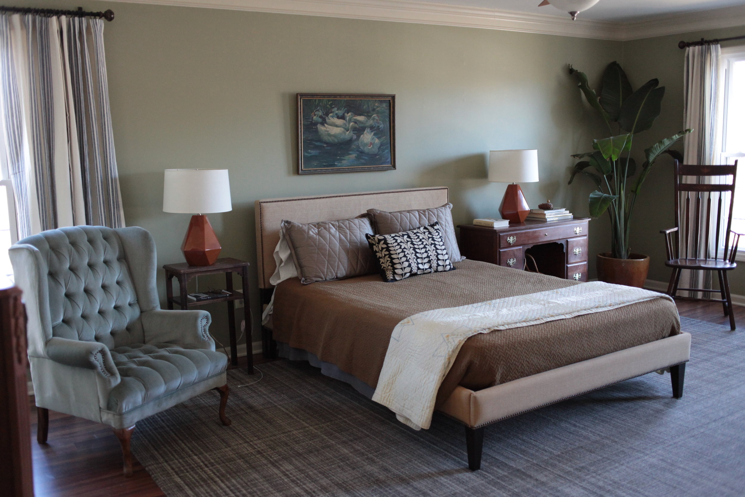 Sage green bedroom with tufted chair, oil painting, orange modern lamps, and Annie Sielke rug