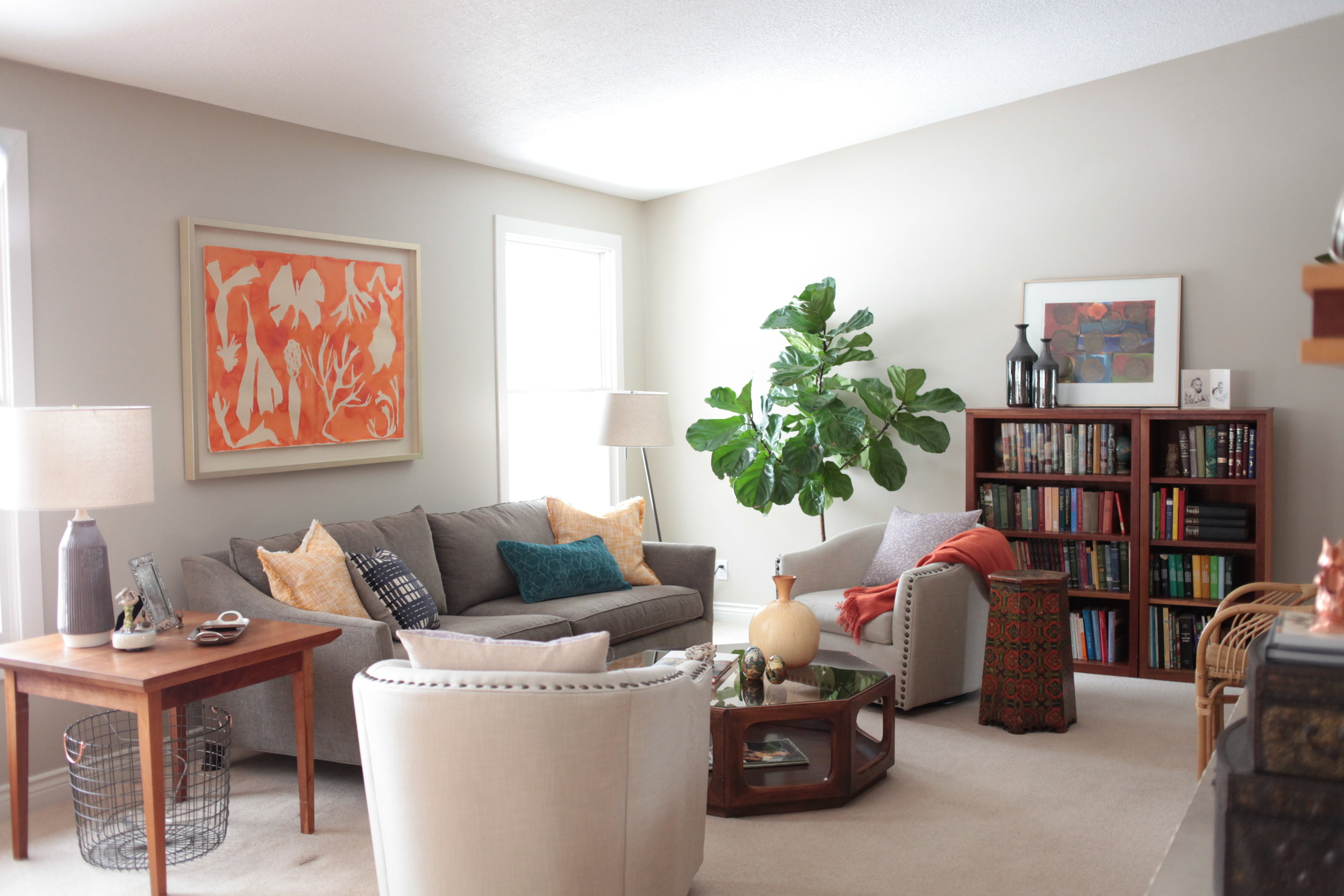A vaulted, neutral, bohemian space with large fireplace, pops of orange, Kate Roebuck watercolor, Pottery Barn Harlow swivel chairs, fig tree, and wicker chair.jpeg.JPG
