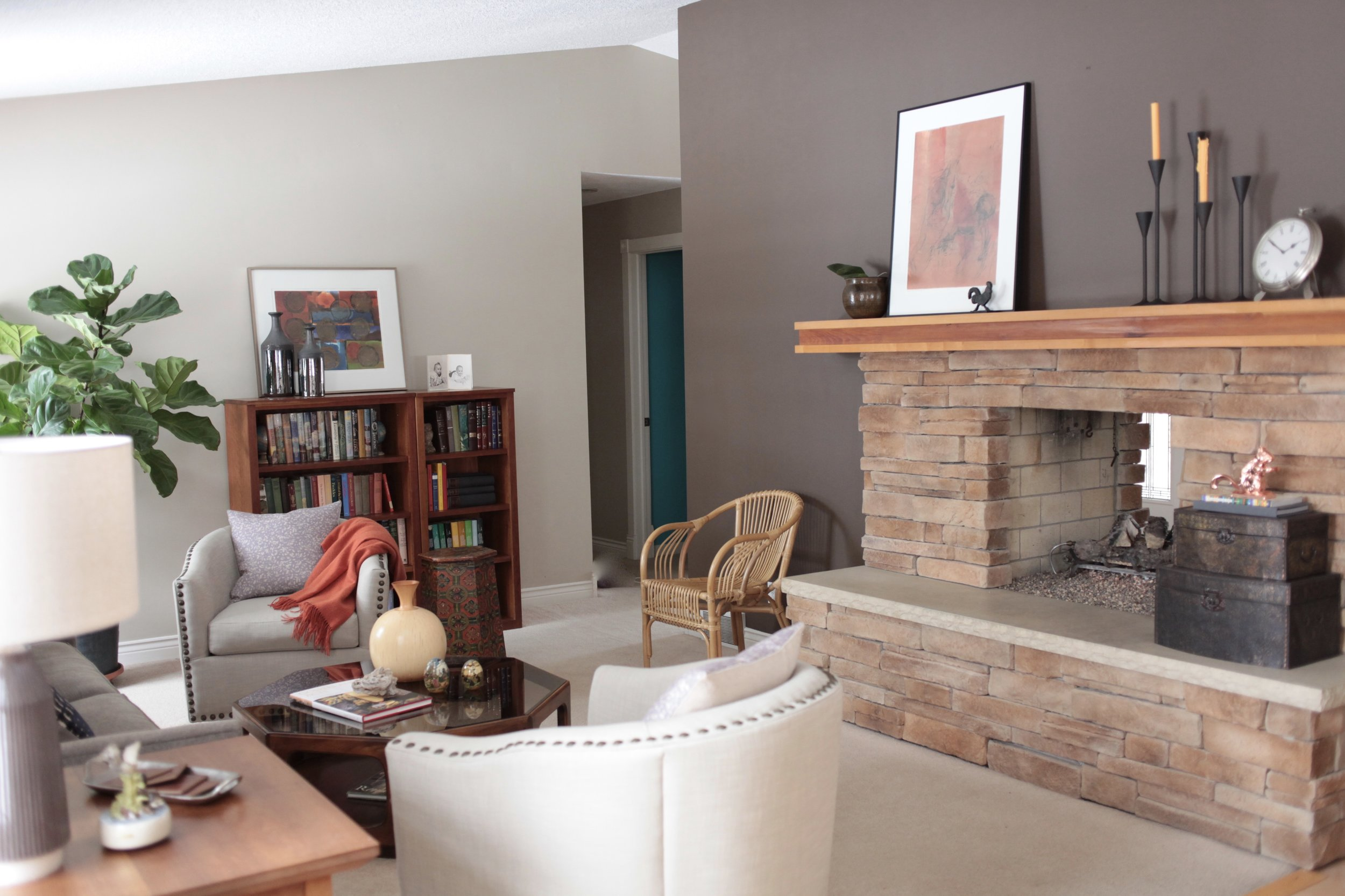 A neutral space with large fireplace, pops of orange, fig tree, and wicker chair.jpeg