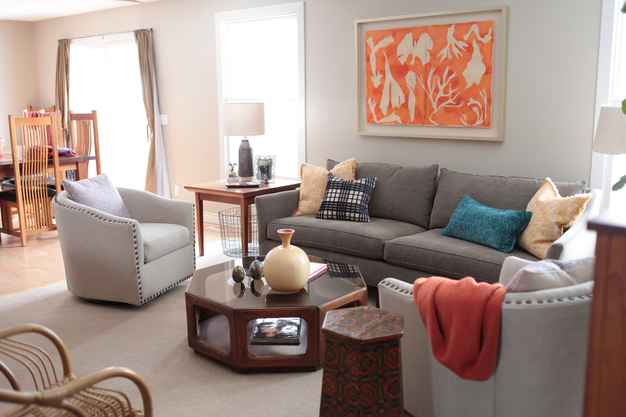 An inviting neutral room with orange art, swivel chairs, and octagon wooden coffee table.JPG