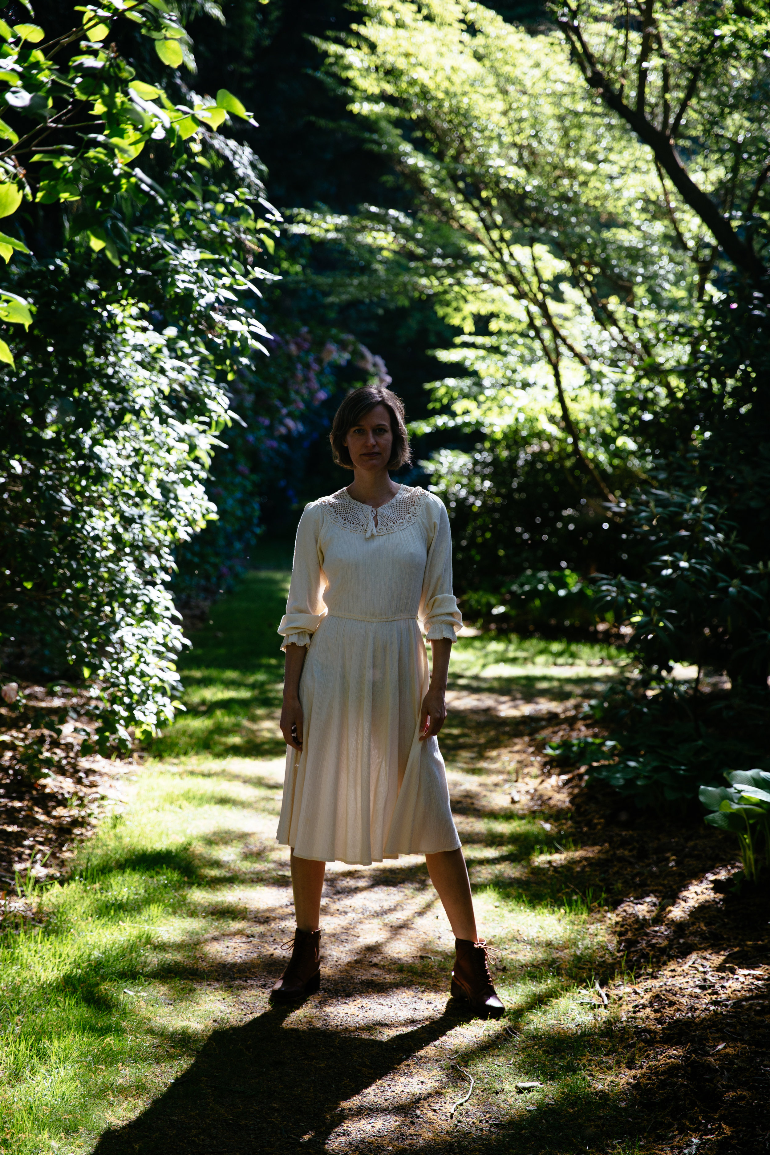 Elaine Schimek among lilacs and hostas