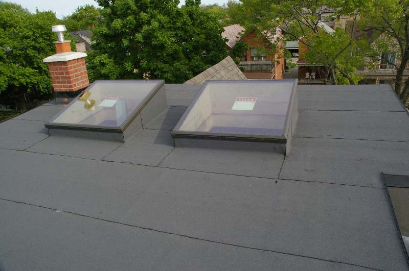 Top flat roof is done and skylights are roofed in.     Skylights aimed away from the sun to decrease heat and allow for a more ambient light. The grey roofing layer is the final sun proof and water proof layer.