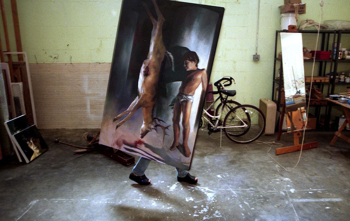 Artist Rima Jabbur moves a painting at her studio in Orlando, FL. Photo by Tom Burton