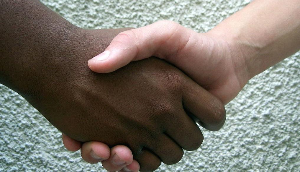 En ljushyad och en mörkhyad hand skakar hand.