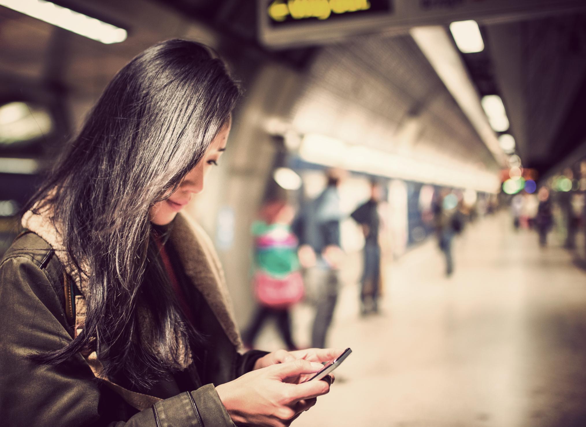 Kvinna som väntar på tunnelbana och läser på sin telefon