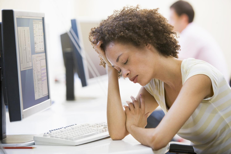 Person framför dator som ser trött ut. Hen sitter i ett kontorslandskap.