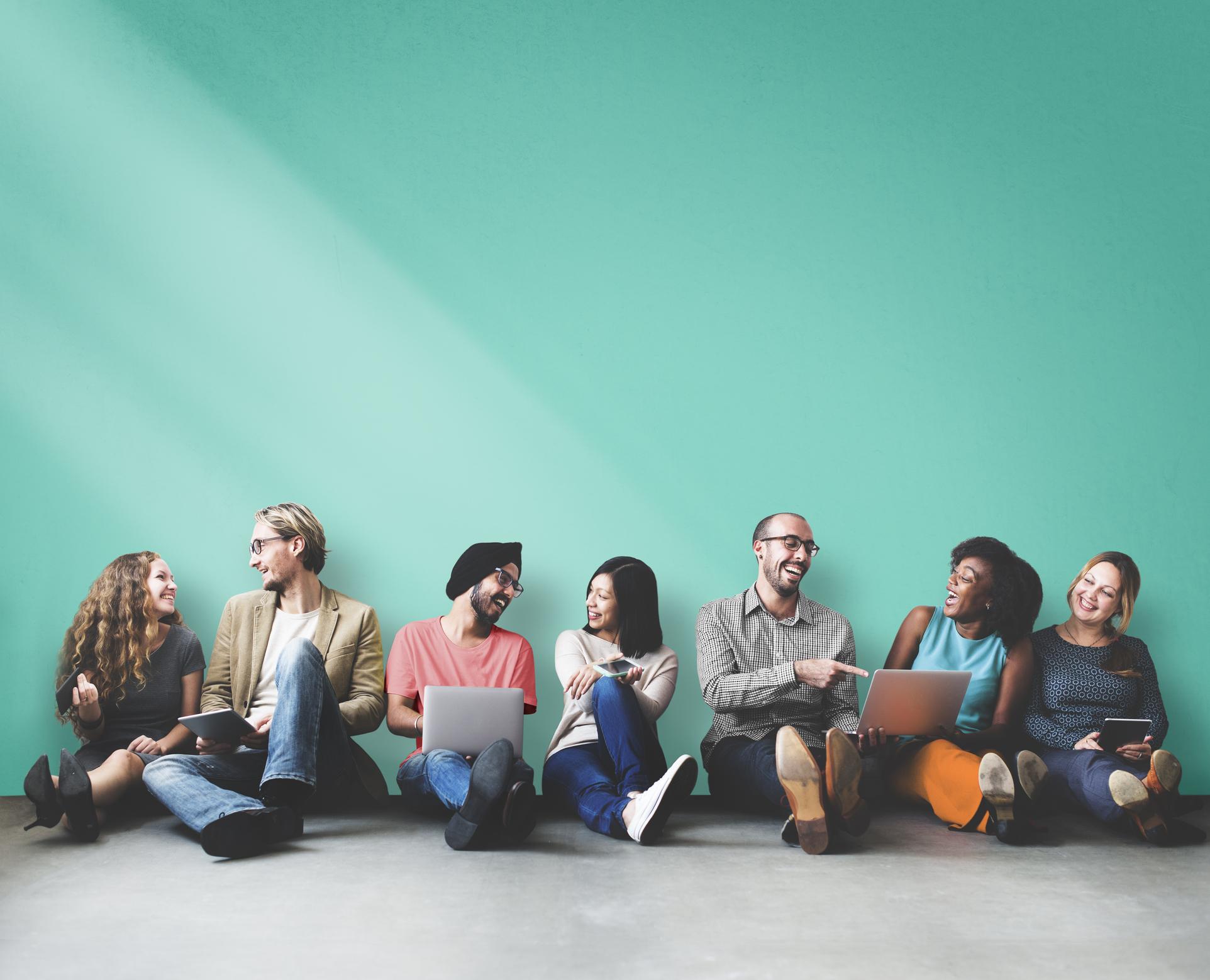 Människor med olika ursprung sitter på rad på golvet. Pratar, skrattar och pekar på laptops som en del har i sina knän.