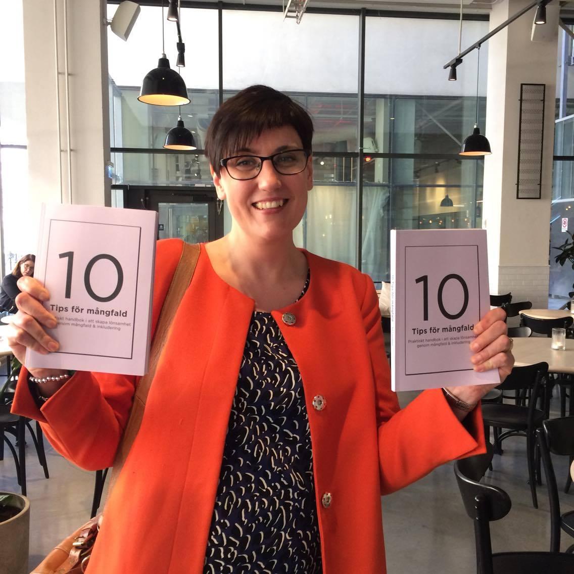 Åsa Gustafsson håller upp boke 10 tips för mångfald