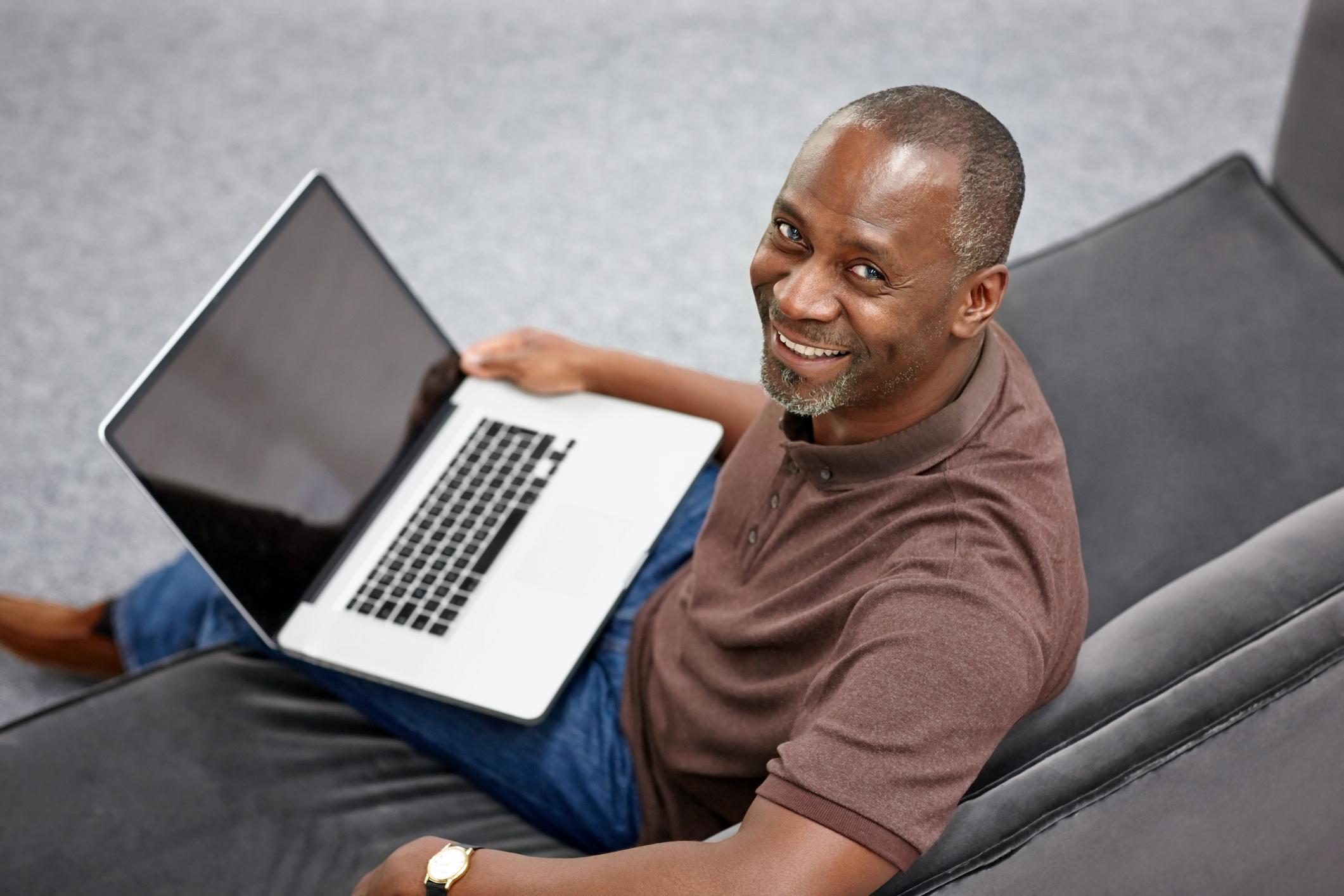 En man sitter i en soffa med en laptop i knäet. Mannen ler och tittar in i kameran.