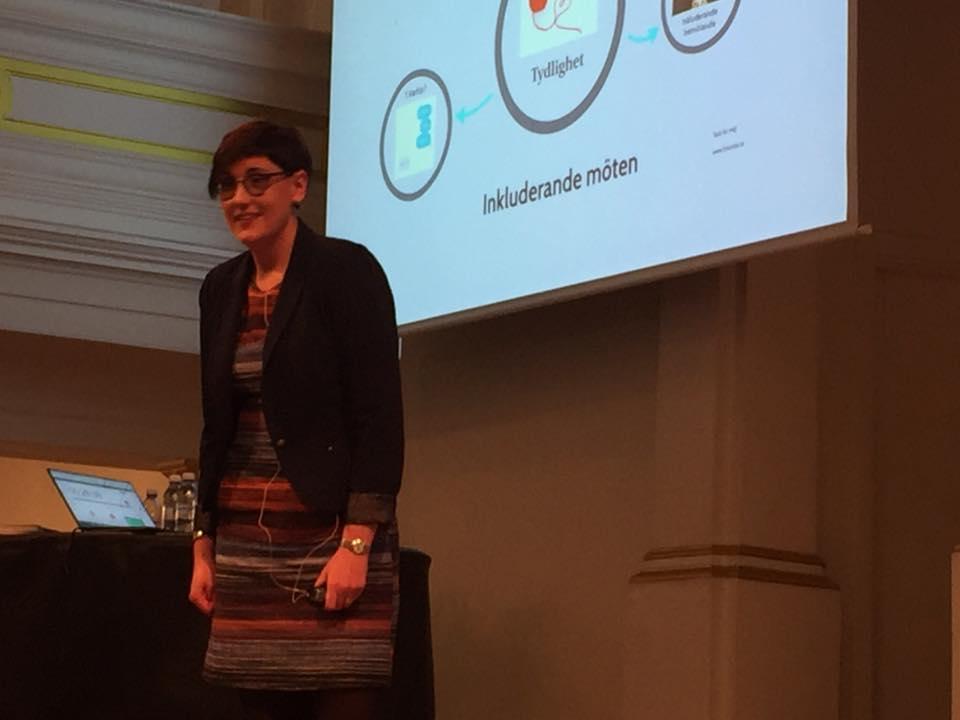 Åsa Gustafsson föreläser om inkluderande möten. Presentationen syns bakom henne.