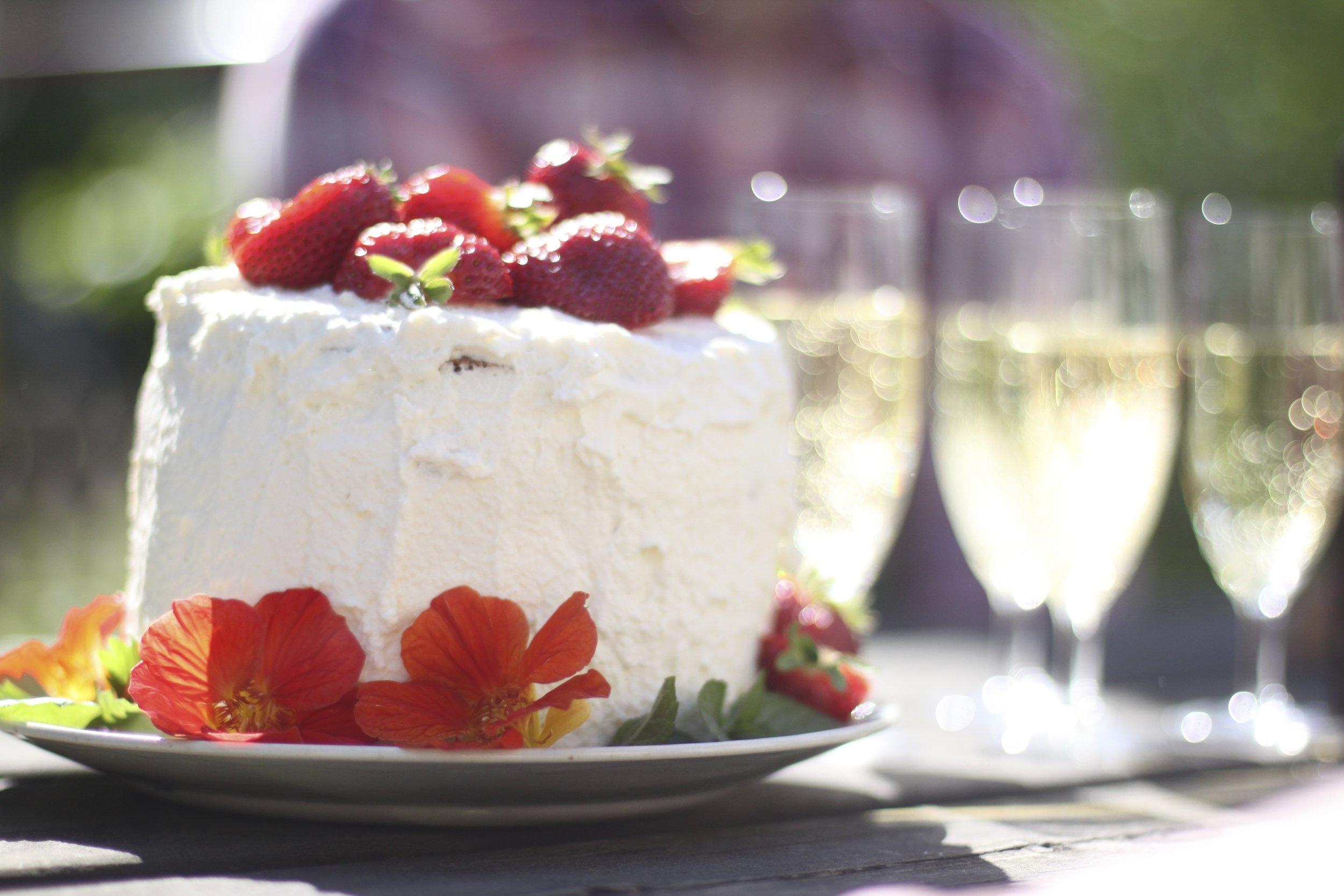 Sommartårta med grädde, jordgubbar och blommor. I bakgrunden syns Champagneglas med bubbel i.