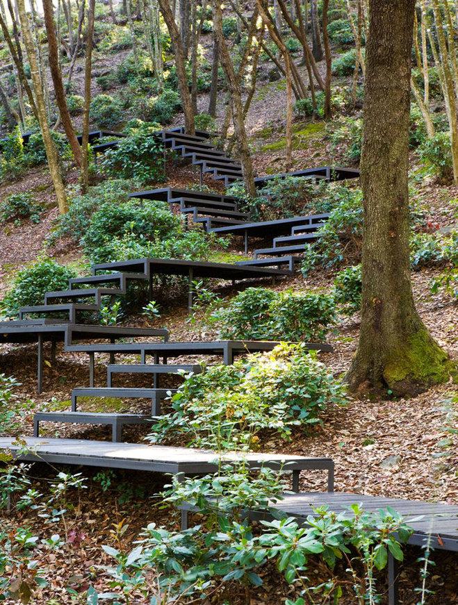 Při stavbách v blízkosti stromů je třeba volit taková řešení, která stromy neohrozí. Příklad schodů kopírující terén kotvených na pilotech. Zdroj: Clive Nichols