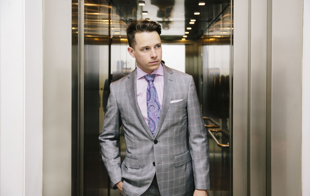 """""""Peter Perry wears a light grey check suit, with a pink cotton shirt, paisley tie and white and pink striped pocket square. Sourced from  M.J. Bale , Peter's ensemble is young, fun but still professional. The pink against the grey is easy on the eye, and suits his skin tones. Check is the big suit story of the moment and the paisley print comeback ties-in well with his overall look. Peter's style draws on his background as a professional golfer where bright colours and checks are the norm. He is young and full of aspirations and this look communicates he's man on a mission."""" – Jeff Lack"""