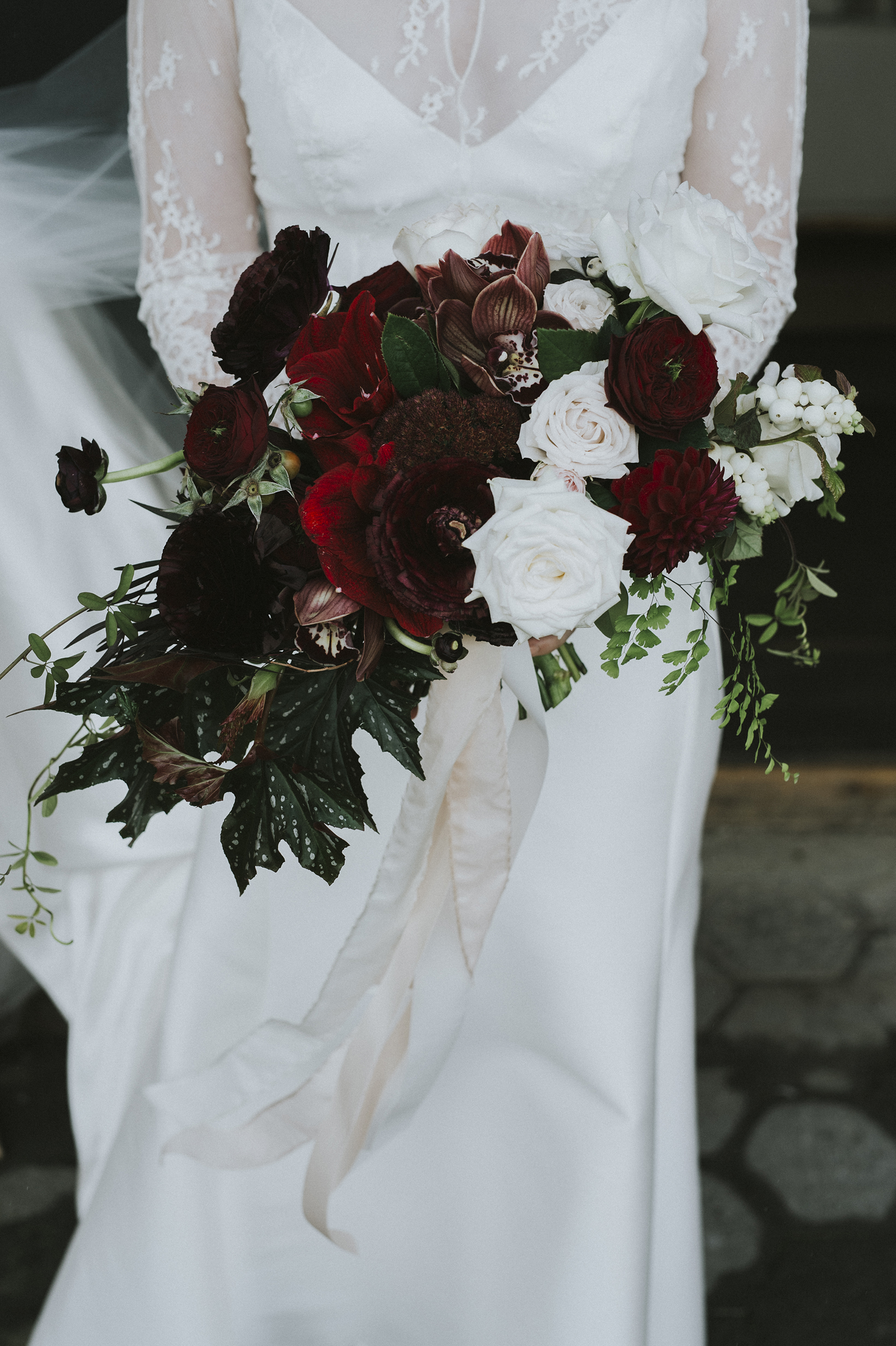 End of Autumn moody bouquet of roses, ranunculas, dahlia, snowberry, orchid, sedum and begonia leaf. Photograph by All Grown Up Weddings.