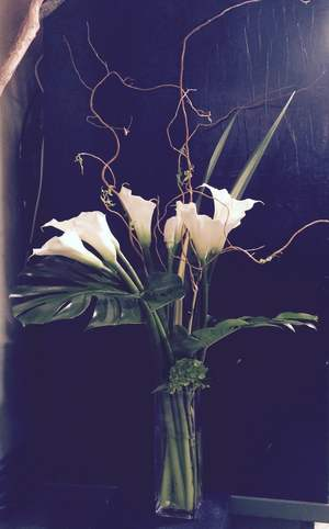 Callas with aspidistra and curly willow arranged in vase