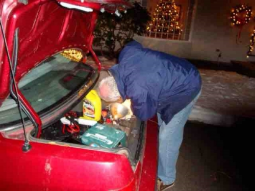 My father fixing a taillight. Look, there's beer in the trunk!