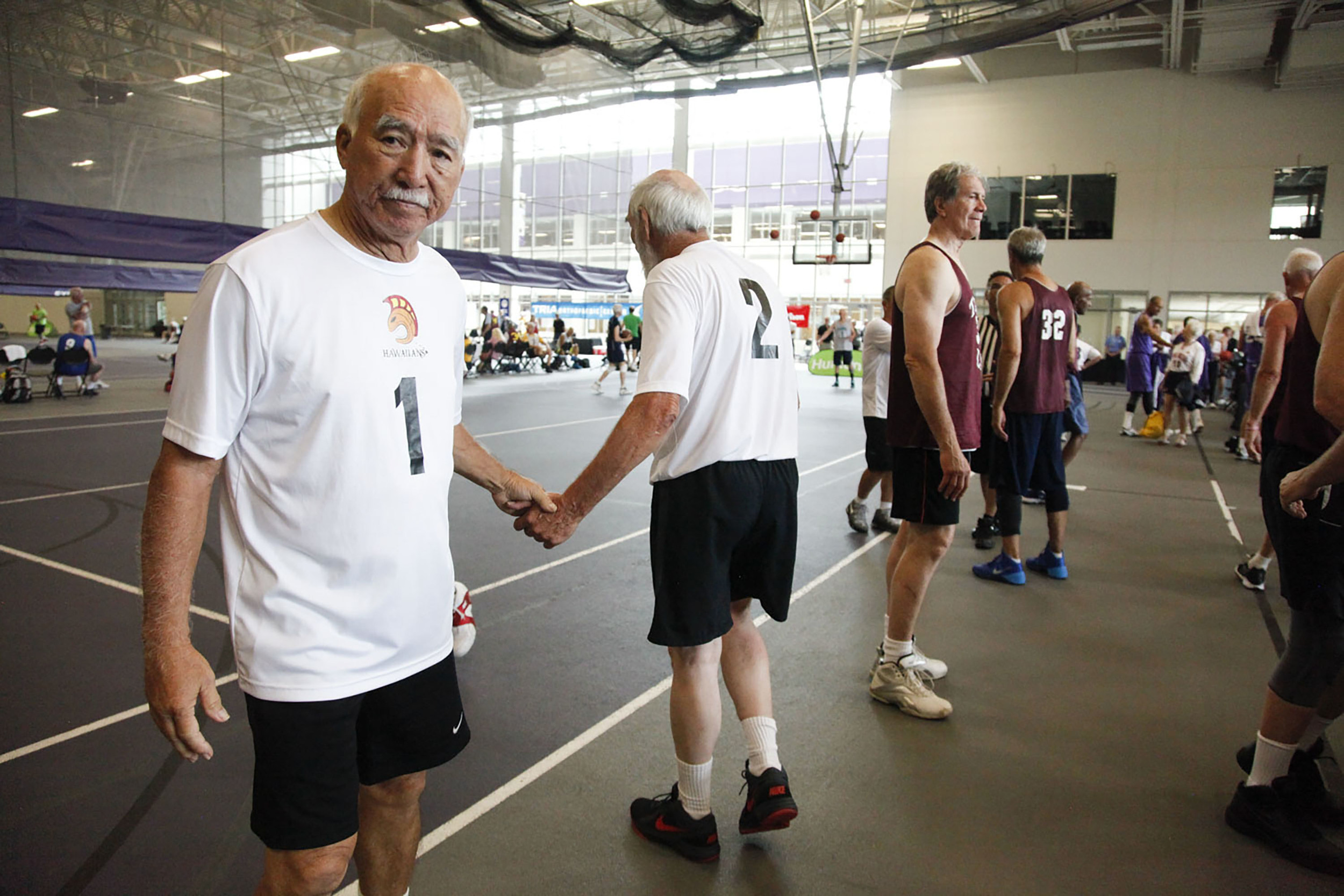 Wayne Kihune (left) and Jerry Schletzbaum (right) of the Hawaiians shake hands after a game against Taylor Law during the National Senior Games basketball competition. This competition took place at the St. Thomas University Basketball Court in St. Paul, MN. on Jul. 9, 2015.