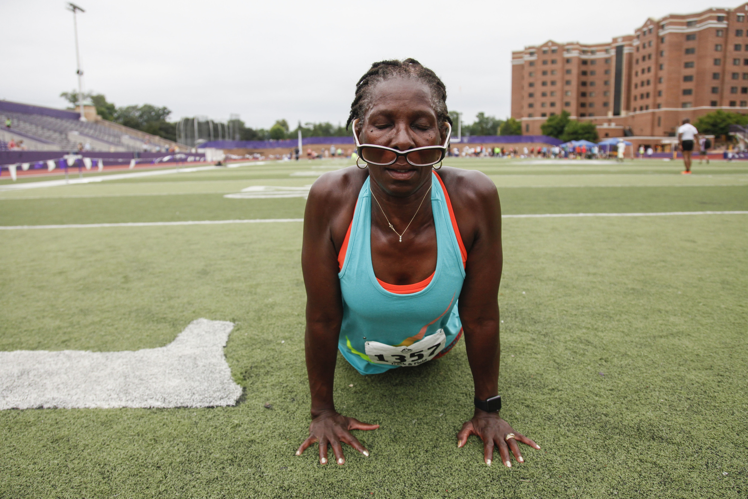 Regina Stewart, a runner participating in the 2015 National Senior Games Track and Field event, stretches in between heats on the St. Thomas University Field in Minneapolis, MN. This event took place on Jul. 14, 2015.